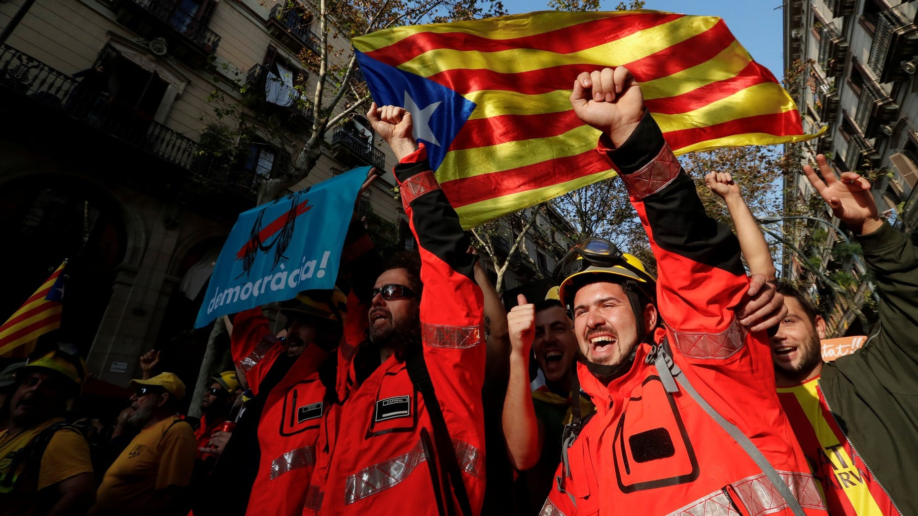 Firemen shout slongans under an Estelada (Catalan separatist flag) during a march in Barcelona, Spain, October 27, 2017.