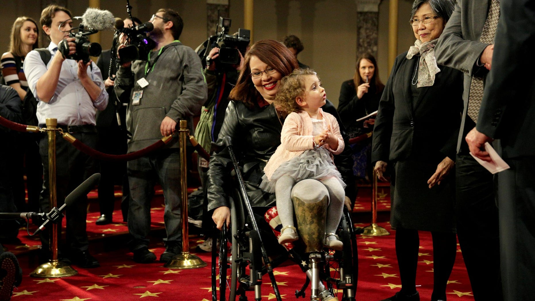 FILE -- Senator Tammy Duckworth (D-IL) carries her daughter Abigail, January 3, 2017.