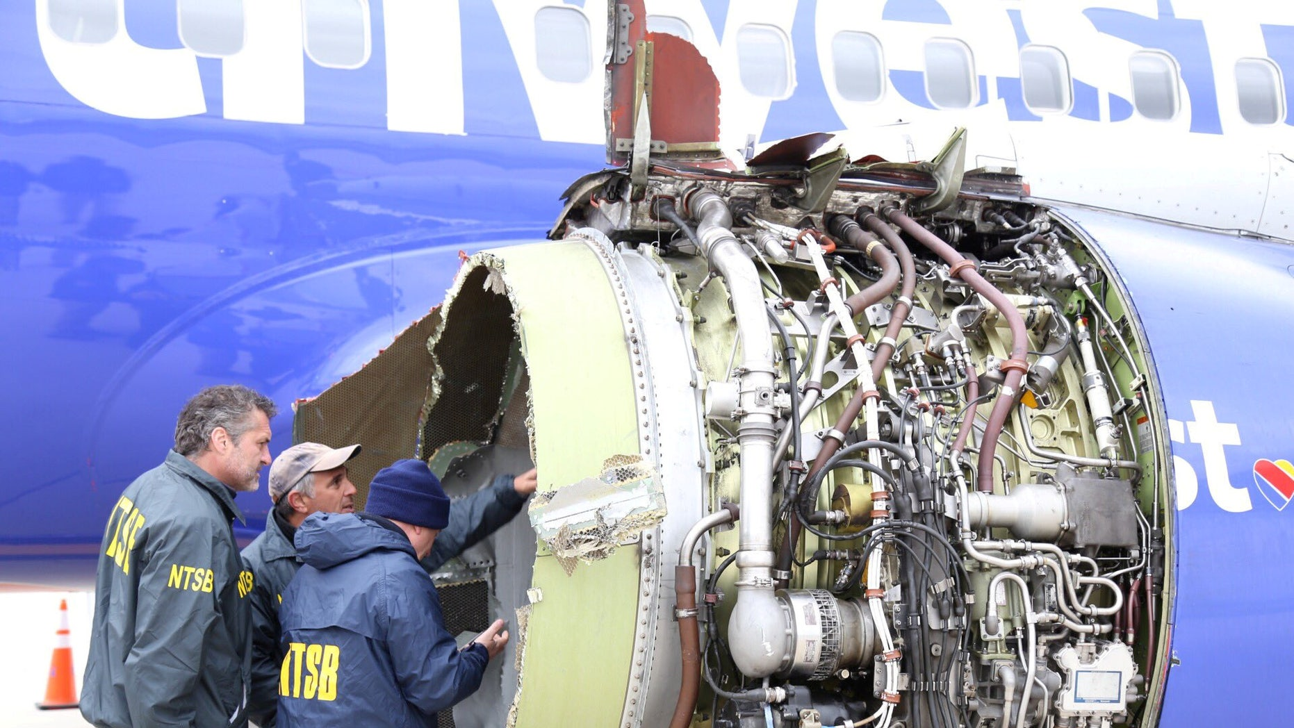 Investigators from the National Transportation Safety Board examine damage to the engine of the Southwest Airlines plane in Philadelphia, April 17, 2018.