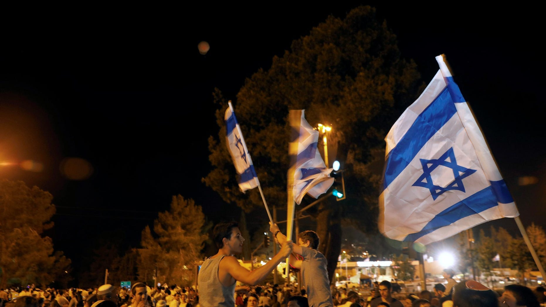 FILE -- Israelis dance with Israeli national flags during celebrations marking Israel's 70th Independence Day in Jerusalem April 18, 2018.