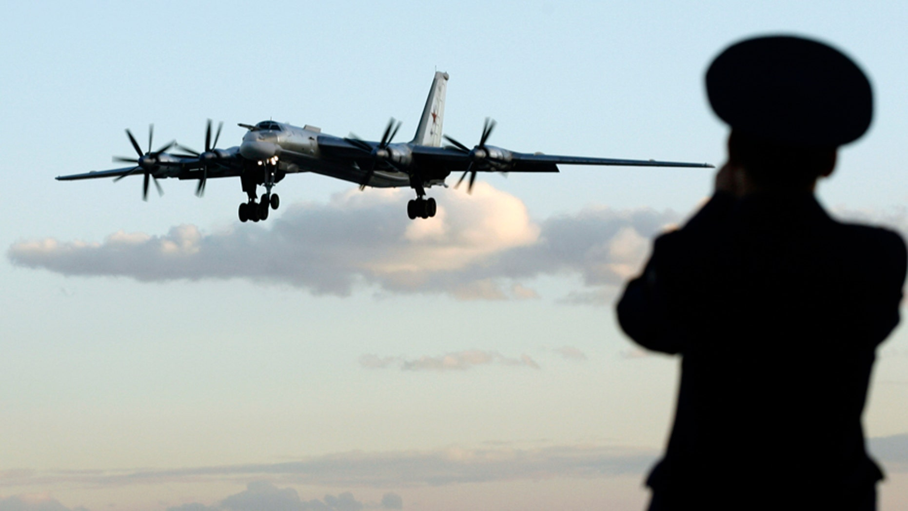 "A Russian officer takes a picture of a Tu-95 bomber, or ""Bear,"" at a military airbase in Engels, some 900 km (559 miles) south of Moscow, August 7, 2008.  Picture taken August 7, 2008. Two Tu-160 jets, known to Russian pilots as ""White Swans"" flew this month from this base on the Volga river to Venezuela, a mission calculated to show Russia was not afraid to flex its military muscles right under the nose of the United States.To match feature RUSSIA-BOMBERS/ REUTERS/Sergei Karpukhin  (RUSSIA) - RTX8W9J"