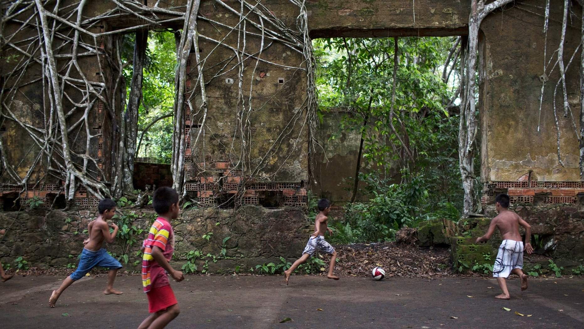 In this May 21, 2014 photo, Children play soccer in the ruins of Paricatuba, near Manaus, Brazil.