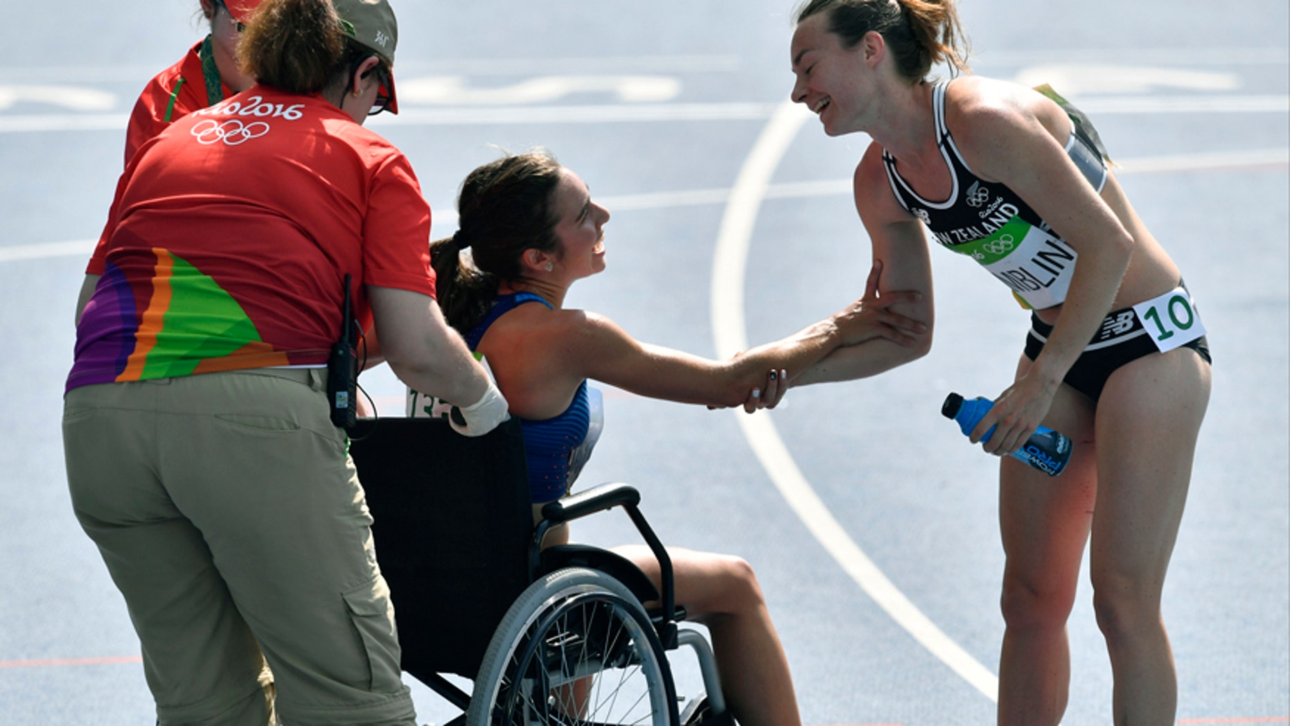 New Zealand's Nikki Hamblin greets the United States' Abbey D'Agostino, left, as she is helped from the track.