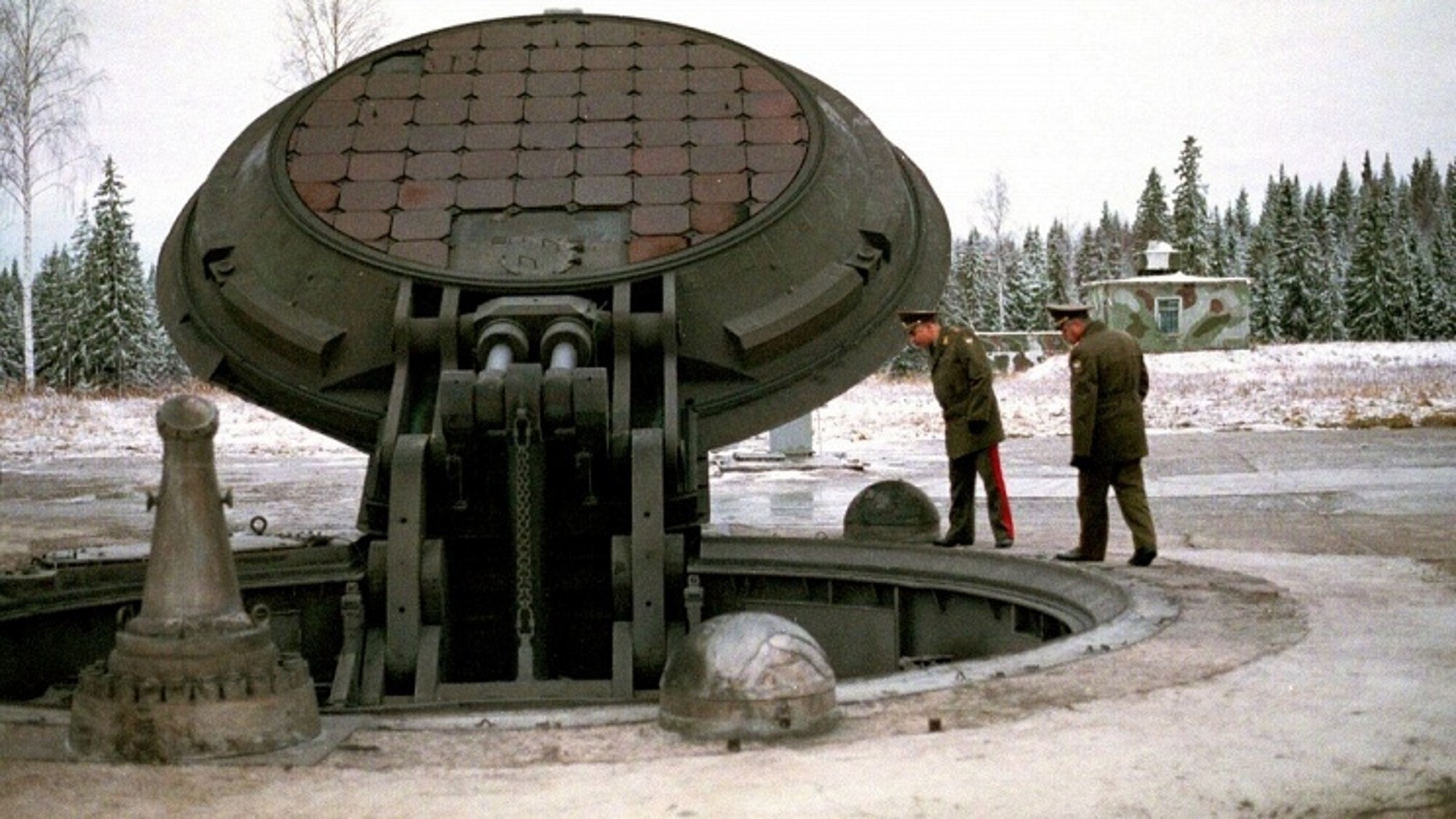Russian high ranking military officials look into an opened silo of a Russian intercontinental ballistic Topol-M missile.