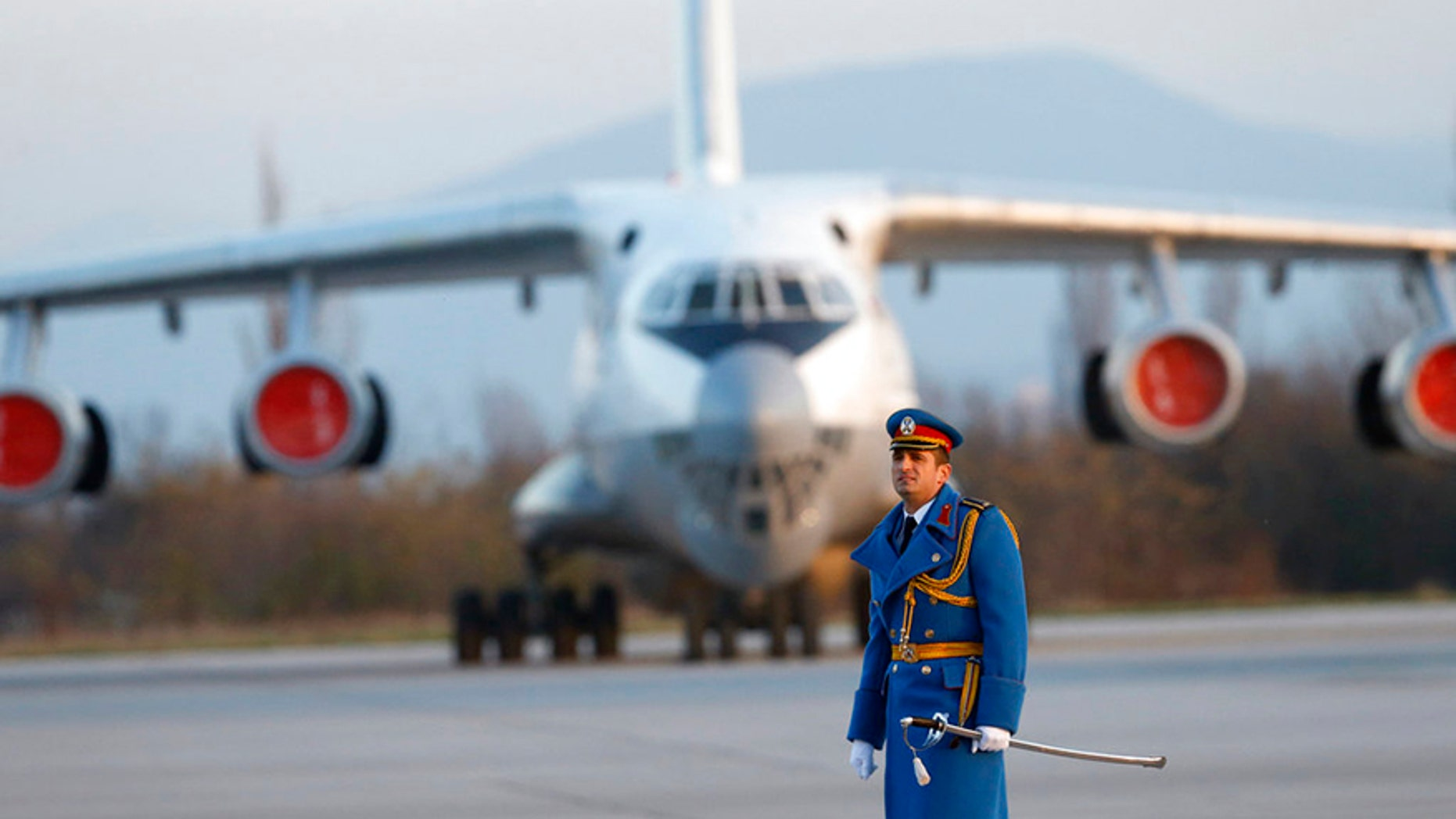 """Serbian army officer walks in front of Soviet made heavy cargo plane Ilyushin Il-76 on the tarmac at the Constantine the Great Airport, near a """"Russian-Serbian Humanitarian Center"""" in Serbia."""