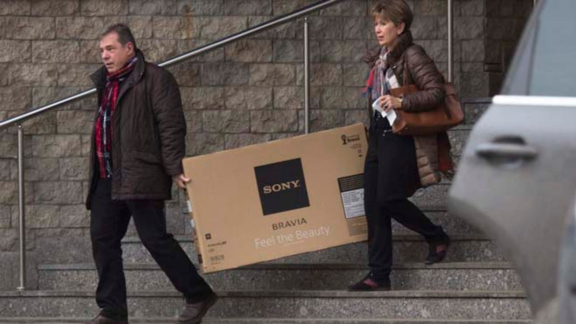 Dec. 17, 2014: A couple carry a television set they purchased from a shop in St. Petersburg, Russia. The collapse of the national currency triggered a spending spree by Russians desperate to buy cars and home appliances before prices shoot higher. Several car dealership were reported to have suspended sales, unsure how far down the ruble will go, while Apple halted all online sales in Russia.