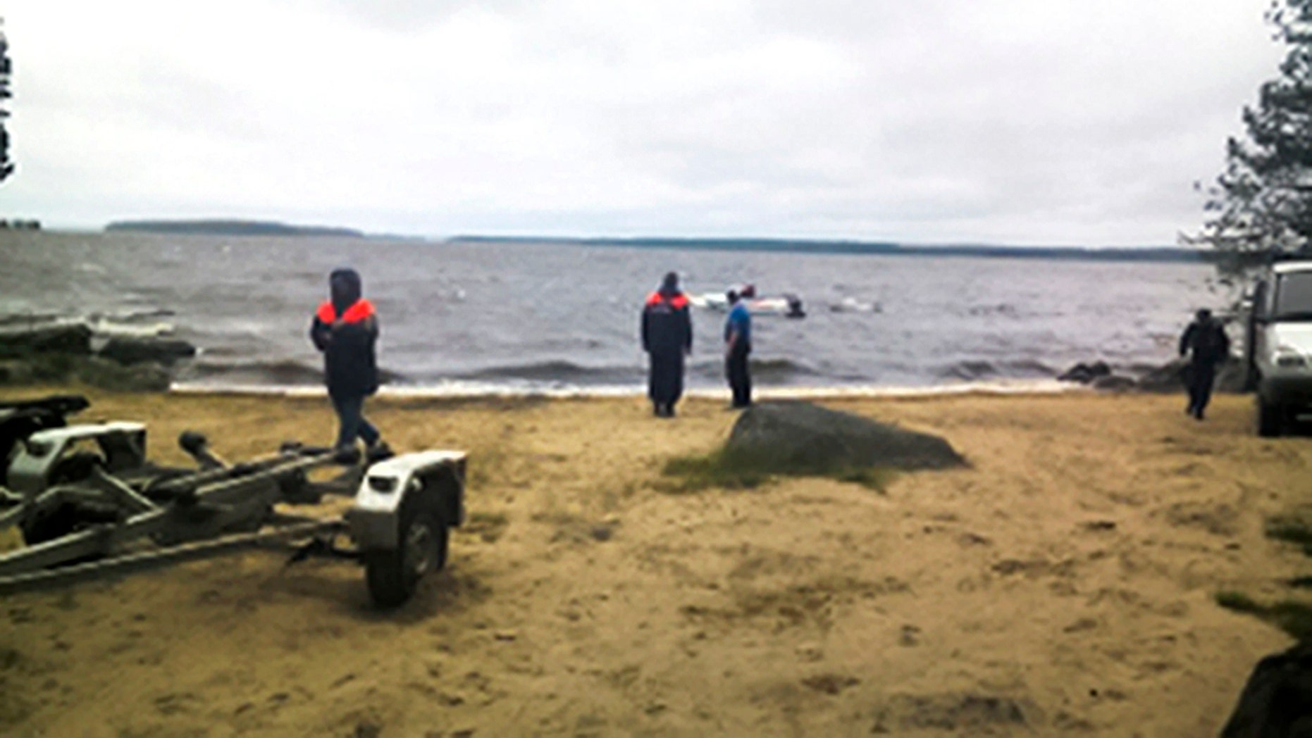 Russian Ministry for Emergency Situations workers stand at the site of an incident at a lake in the Karelia region.