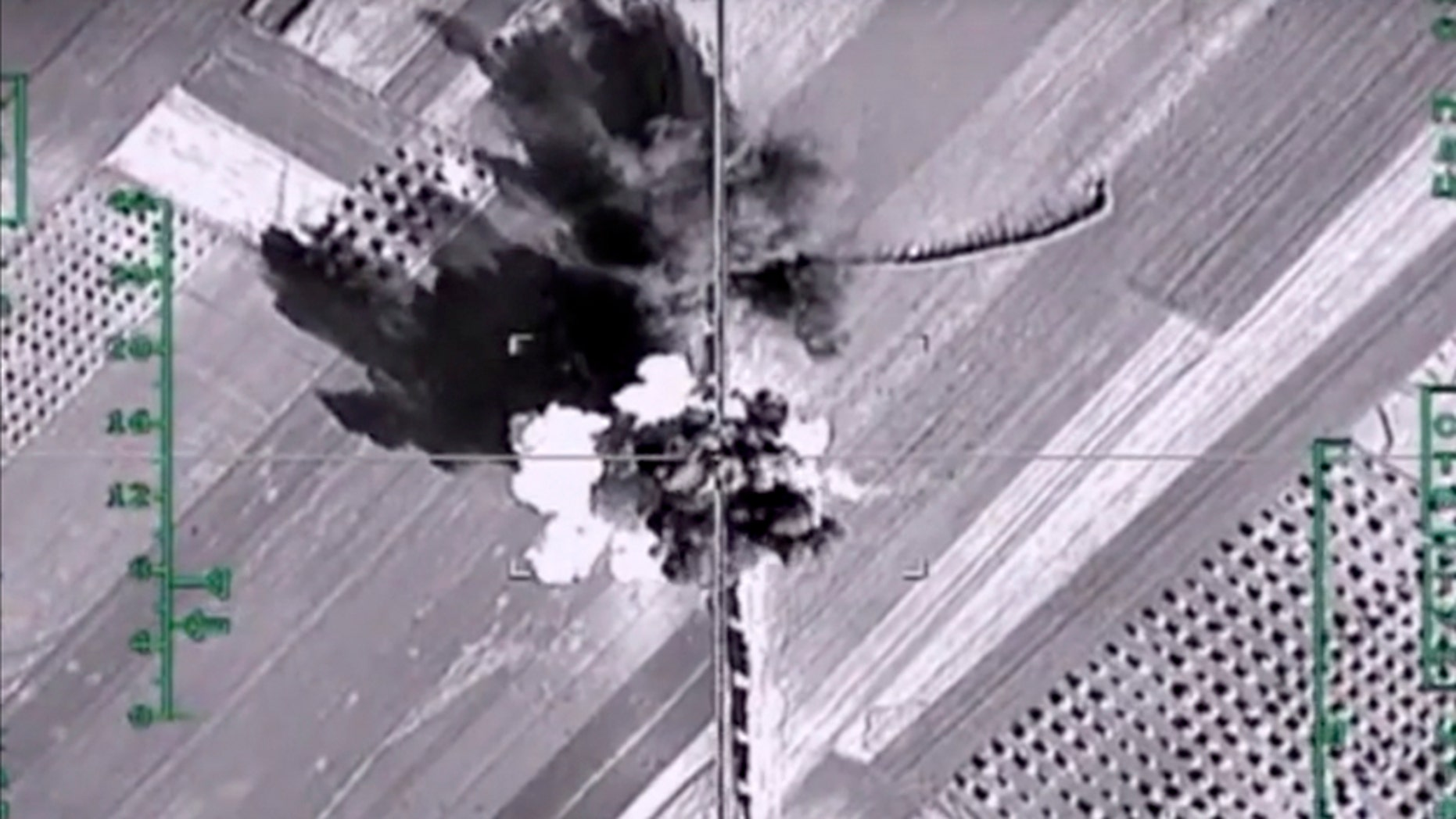 In this photo made from the footage taken from Russian Defense Ministry official web site on Monday, Feb. 1, 2016, an aerial image shows what it says is a column of heavy trucks carrying ammunition hit by a Russian air strike near Aleppo, Syria.
