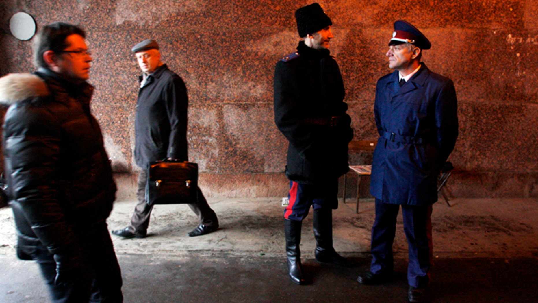 Nov. 27, 2012: Two Russian Cossacks, right, watch pedestrians passing by as they patrol Belorussky railway station in downtown Moscow, Russia.