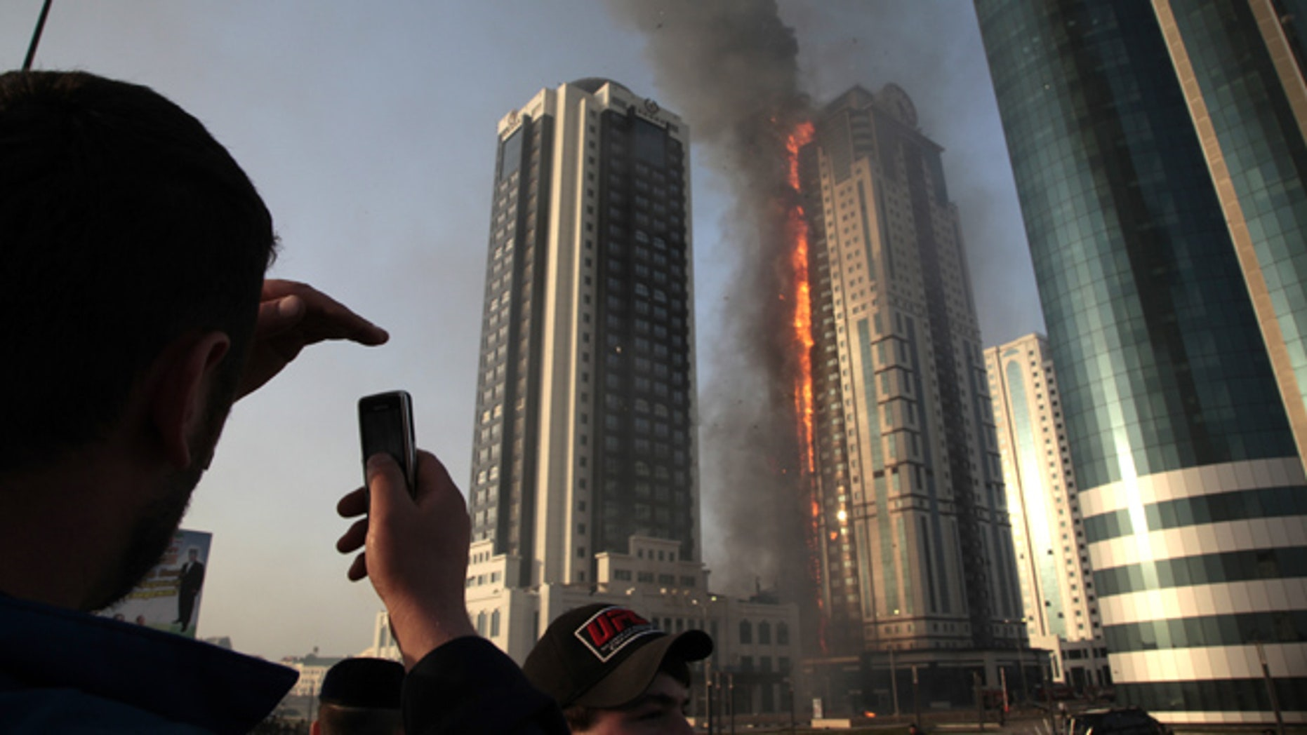 April 3, 2013: A local resident makes photos with a mobile phone of a fire in a high-rise apartment building in provincial capital Grozny, Russia. French actor Gerard Depardieu reportedly received an apartment in the complex of buildings as a gift from Chechen leader Ramzan Kadyrov.