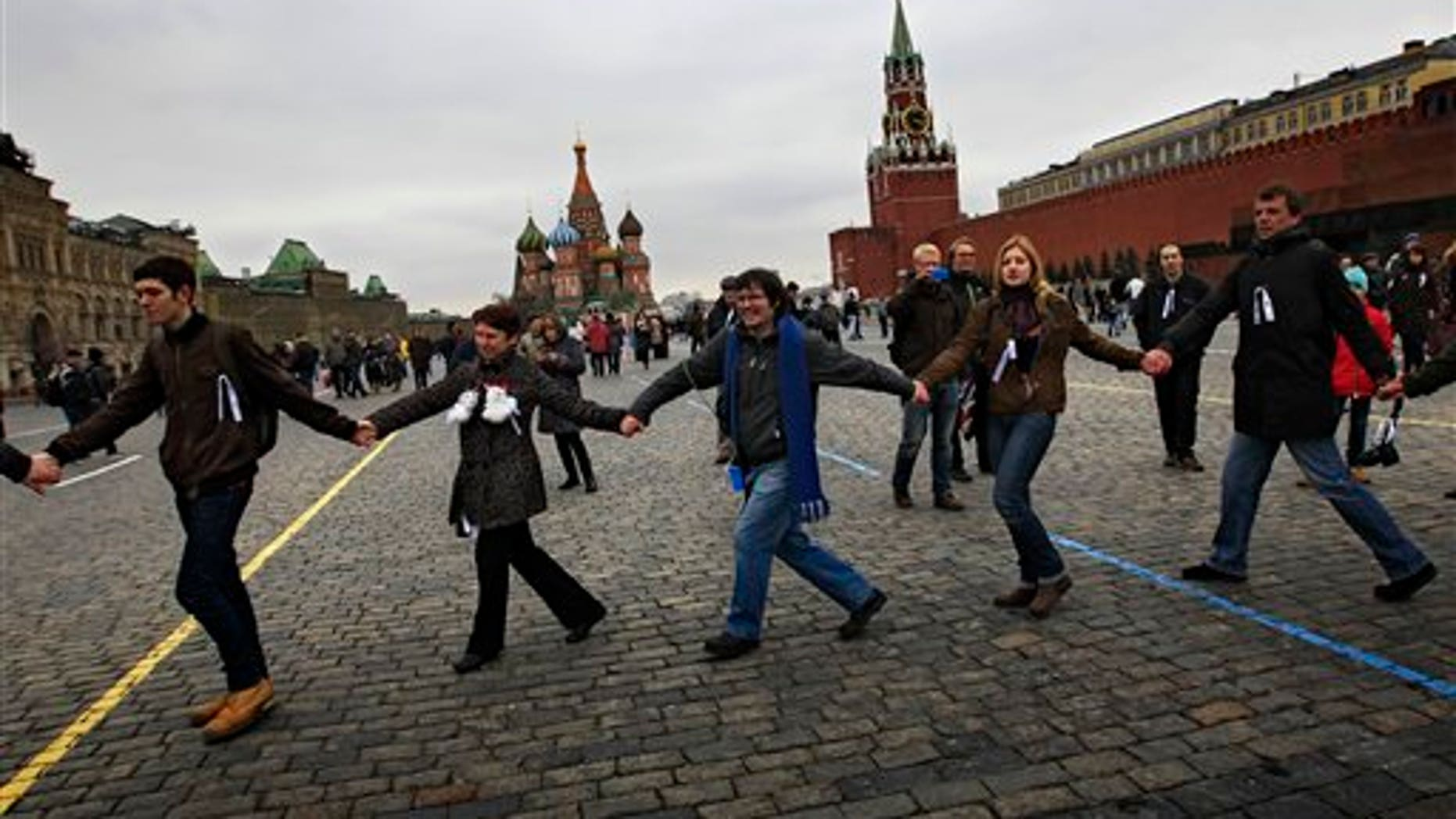 April 8, 2012: Opposition supporters wearing white ribbons walk in a circle hand to hand during a protest at the Red Square in Moscow. Opposition activists called for supporters to walk around Red Square on Sunday wearing the white ribbons that have become a symbol of the protest movement against Prime Minister Vladimir Putin.
