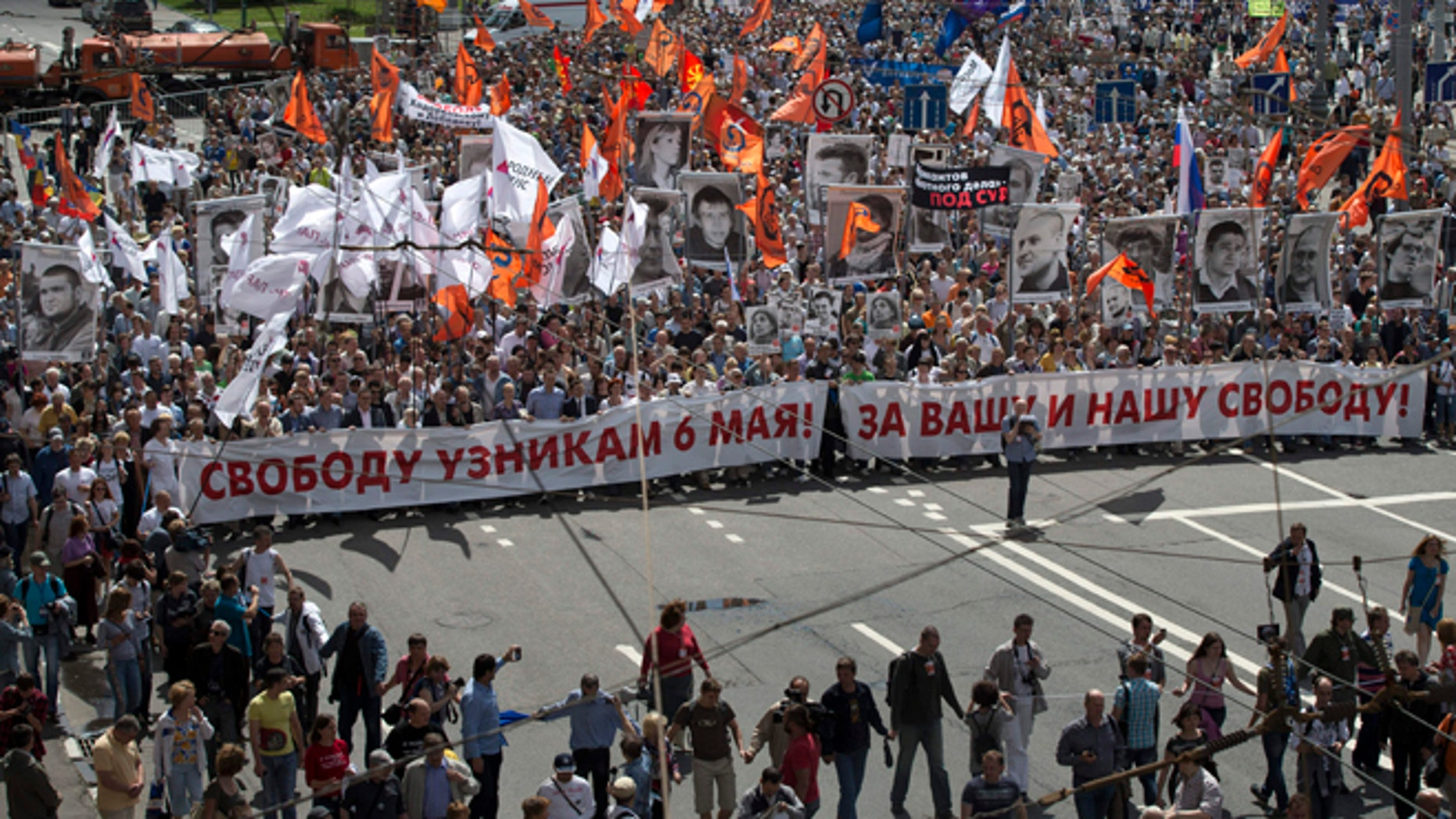 June 12, 2013: Russian opposition protesters some holding portraits of political prisoners  shout anti-Putin slogans as they march through a street next to the Kremlin in Moscow. Thousands of Russian opposition activists are marching through Moscow decrying President Vladimir Putin's authoritarian rule and calling for the release of people they consider political prisoners.