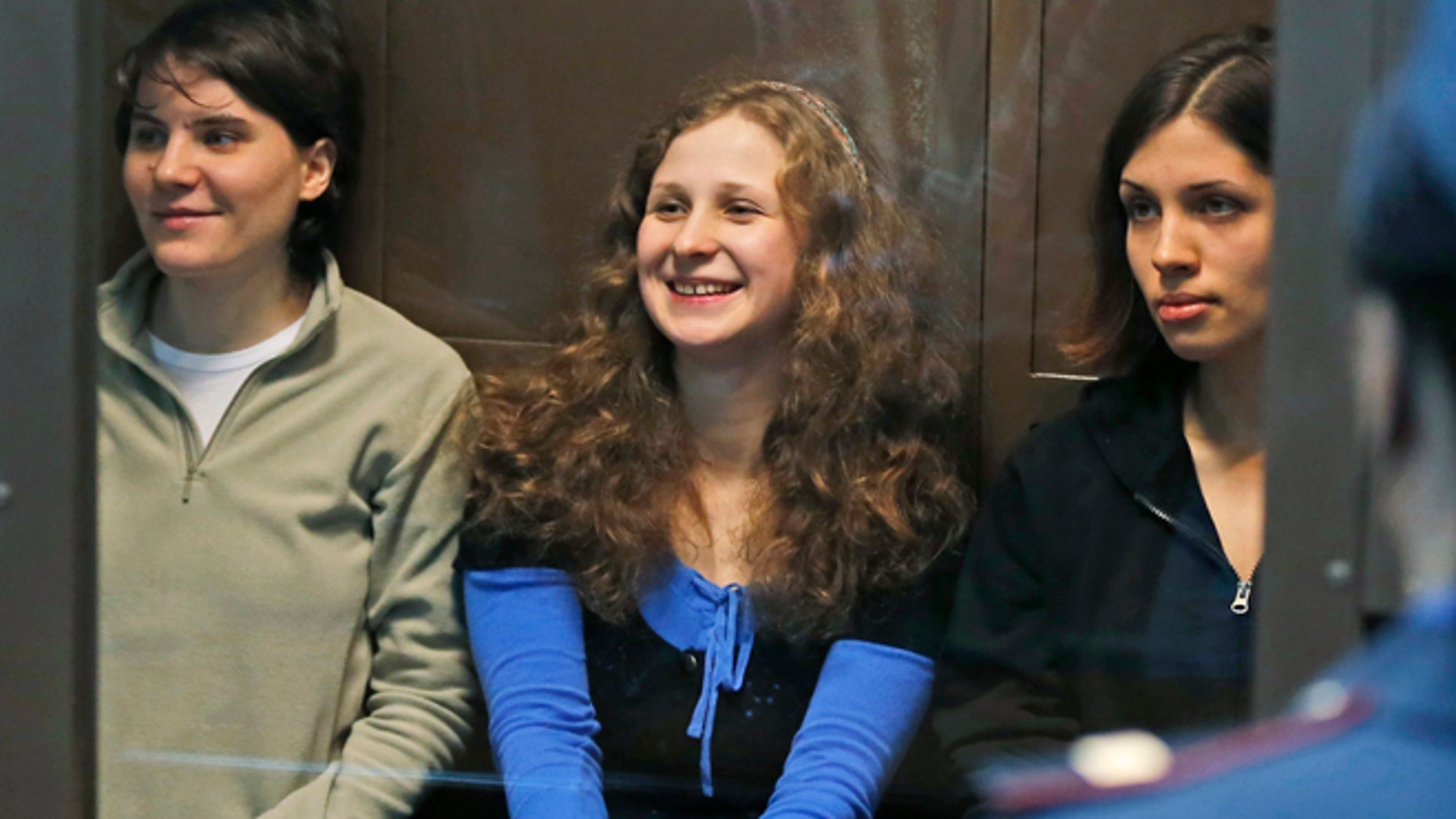 In this Wednesday, Oct. 10, 2012 file photo, feminist punk group Pussy Riot members, from left, Yekaterina Samutsevich, Maria Alekhina and Nadezhda Tolokonnikova sit in a glass cage at a court room in Moscow, Russia.
