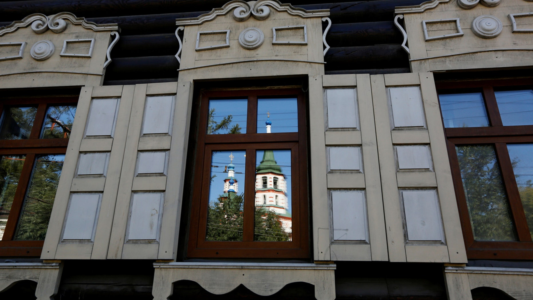 The Feast of the Holy Cross Church is reflected in a window of a 19th century wooden house in the center of the East Siberian city of Irkutsk, Russia, September 8, 2016. REUTERS/Ilya Naymushin - RTSO0O5