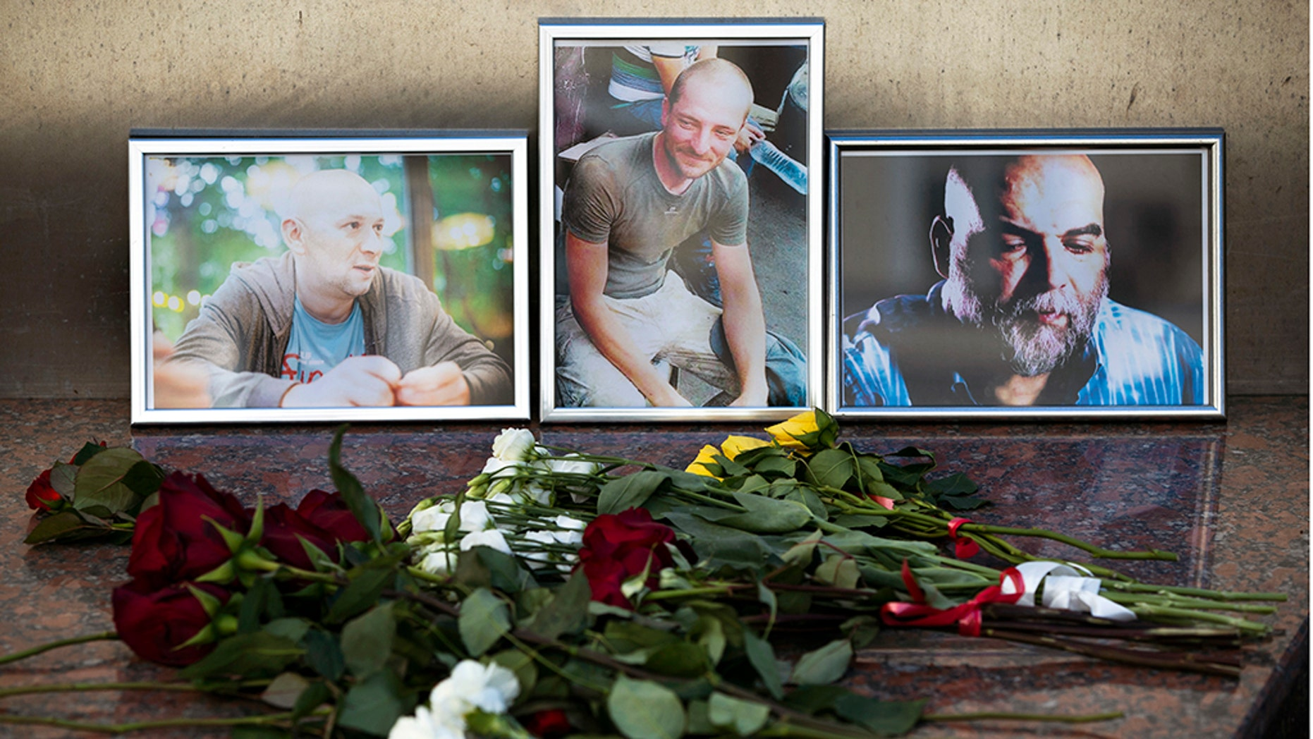 Flowers are placed by portraits of slain journalists Alexander Rastorguyev, Kirill Radchenko and Orkhan Dzhemal, at the Russian journalists Union building in Moscow, Russia, Wednesday, Aug. 1, 2018.