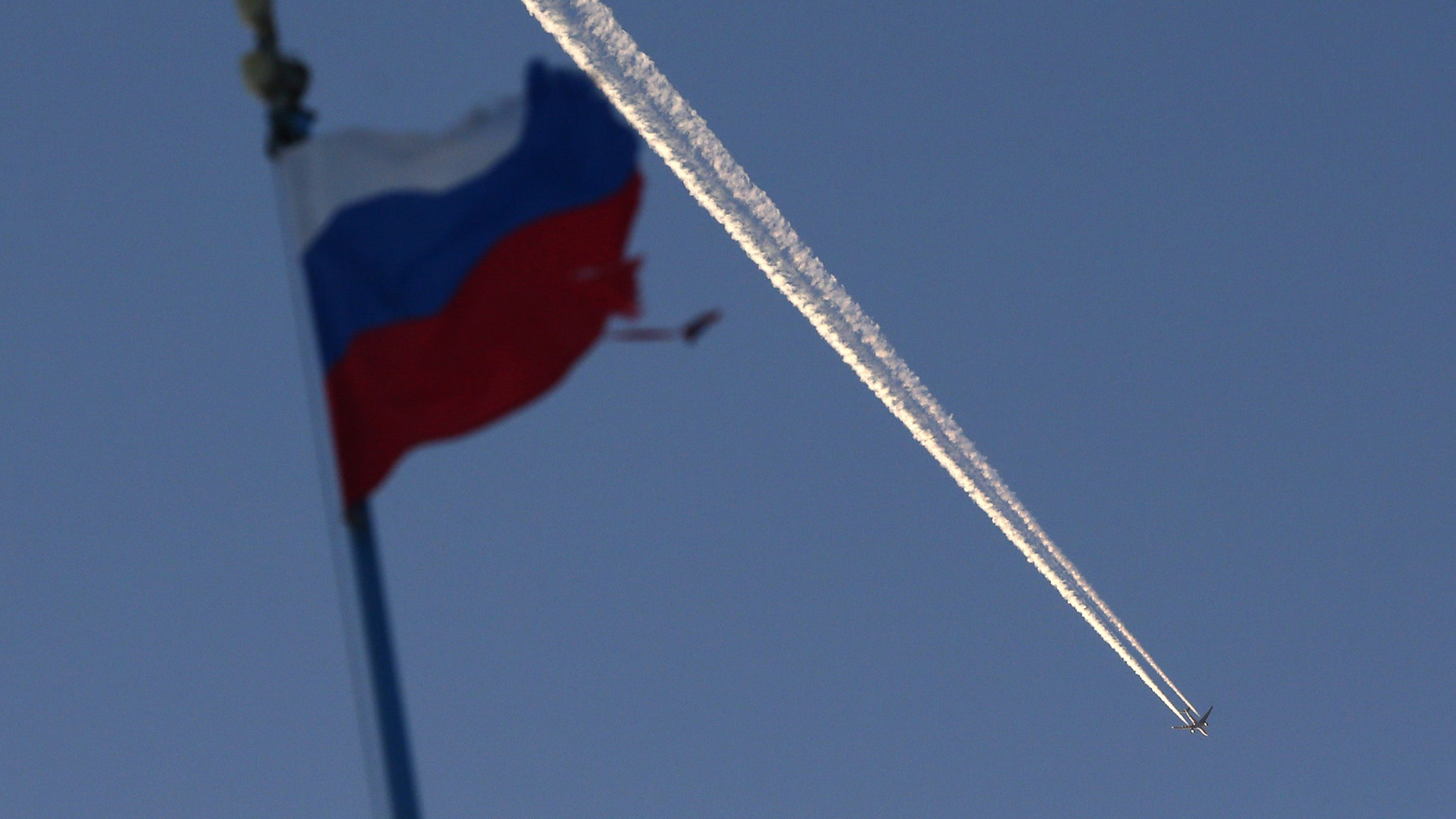 File photo - The Russian state flag flutters, with a plane flying in the sky in the background, outside the Siberian city of Krasnoyarsk, Russia Jan. 27, 2018. (REUTERS/Ilya Naymushin)