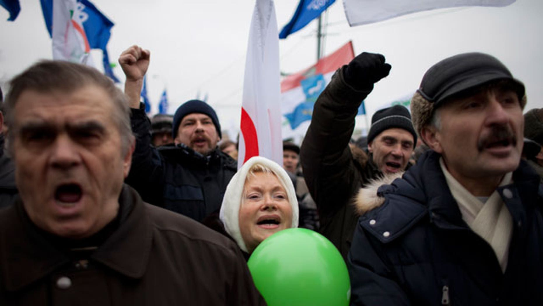 Dec. 17, 2011: With Yabloko party flags in the background, Russian protesters shout slogans during a rally to protest against alleged vote rigging at Bolotnaya Square, on an island in the Moscow River adjacent to the Kremlin in Moscow, Russia.