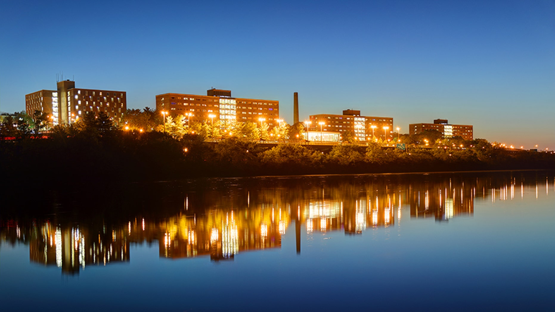 Night view of the Rutgers University campus Halls reflecting on a calm Raritan River