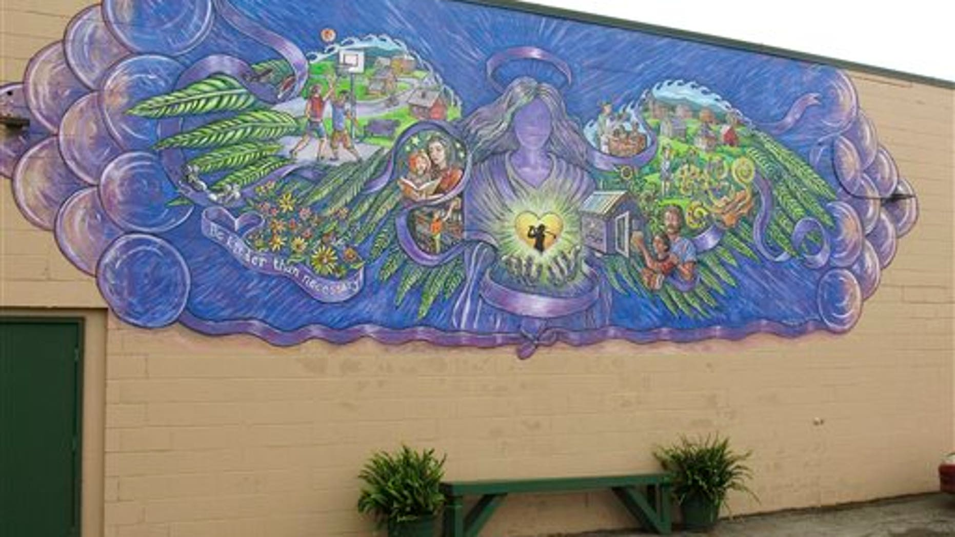 In this Oct. 1, 2015 photo, a mural covers the wall of a store in Rutland, Vt., commemorating the life of 17-year-old Carly Ferro, a star athlete, who was hit by a car and killed while leaving her job at the store. (AP Photo/Wilson Ring)