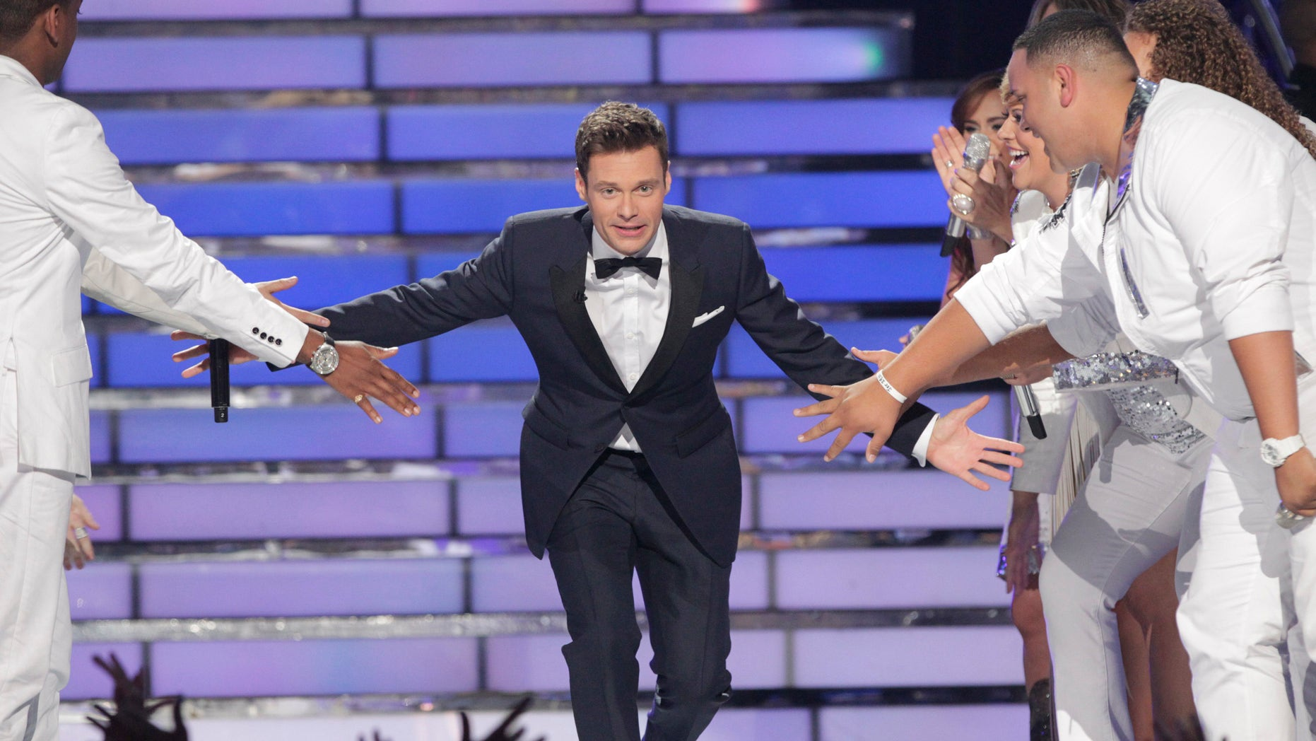 """Host Ryan Seacrest arrives on the stage during the 11th season finale of """"American Idol"""" in Los Angeles, California, May 23, 2012. REUTERS/Mario Anzuoni (UNITED STATES  - Tags: ENTERTAINMENT) - RTR32JHI"""