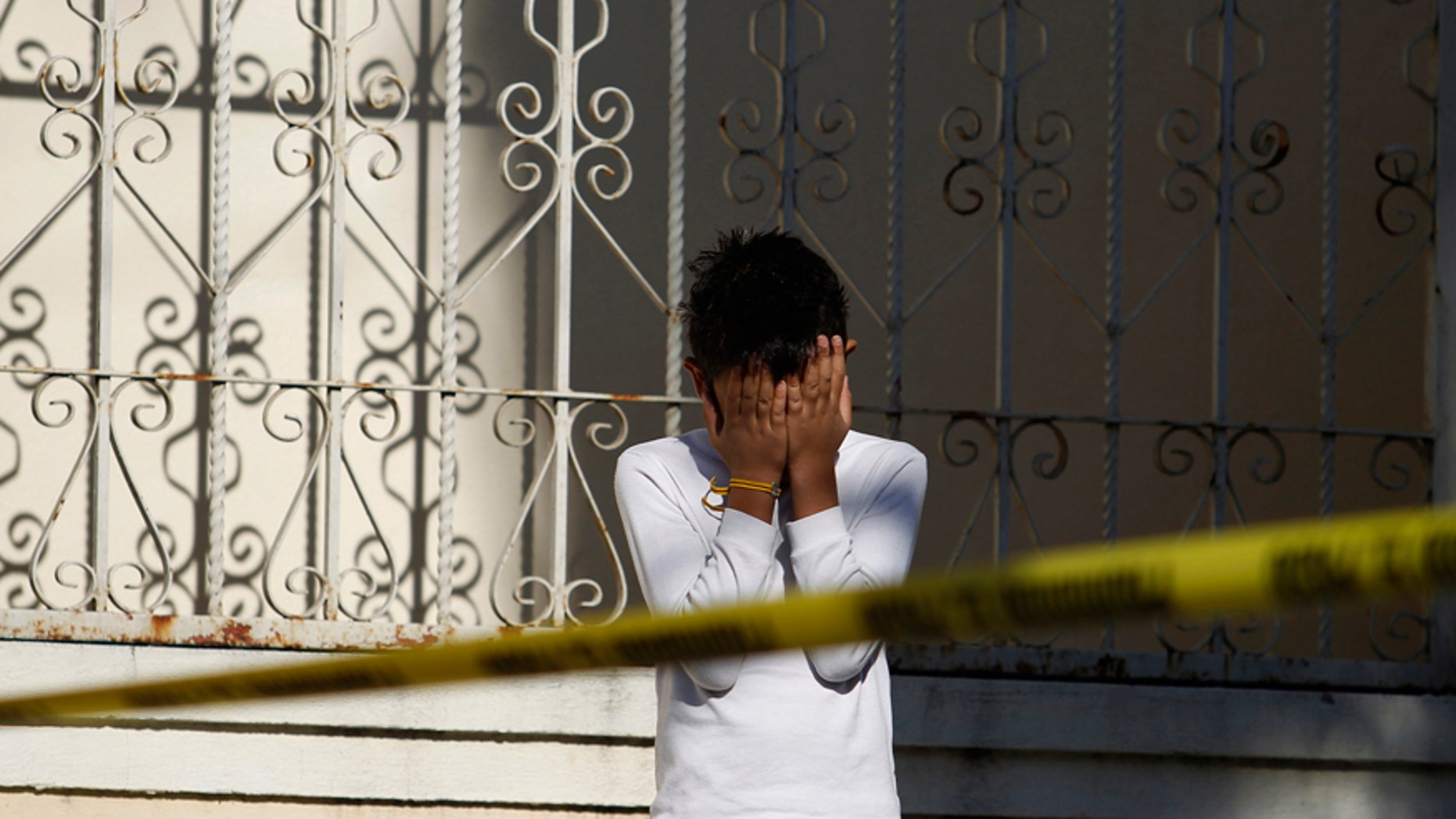 A child covers his face as he stands next to a police cordon at a crime scene where the slain body of a man is found, in Monterrey November 10, 2011. Residents reported that unknown assailants left the body with signs of torture in a park bench, local media reported. REUTERS/Tomas Bravo (MEXICO - Tags: CIVIL UNREST CRIME LAW) - RTR2TURI