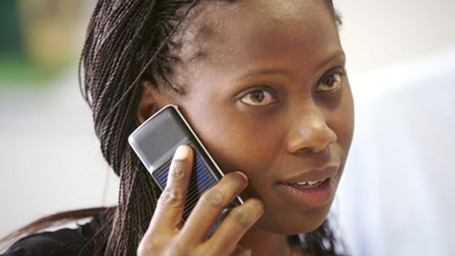 A Safaricom client uses a solar-charged mobile phone handset at a retail centre in Kenya's capital Nairobi, in this September 22, 2009 file photo. Solar cellphones could build on the economic advantages that mobile phones have already brought to far-flung regions of Africa and the Indian subcontinent, including price transparency and more accurate and timely information. Mobile phone penetration in these regions has been held back by a lack of electricity: there is simply no way to charge a cellphone in many rural areas of developing countries. To match feature CELLPHONES-SOLAR/. REUTERS/Thomas Mukoya/Files (KENYA BUSINESS SCI TECH)