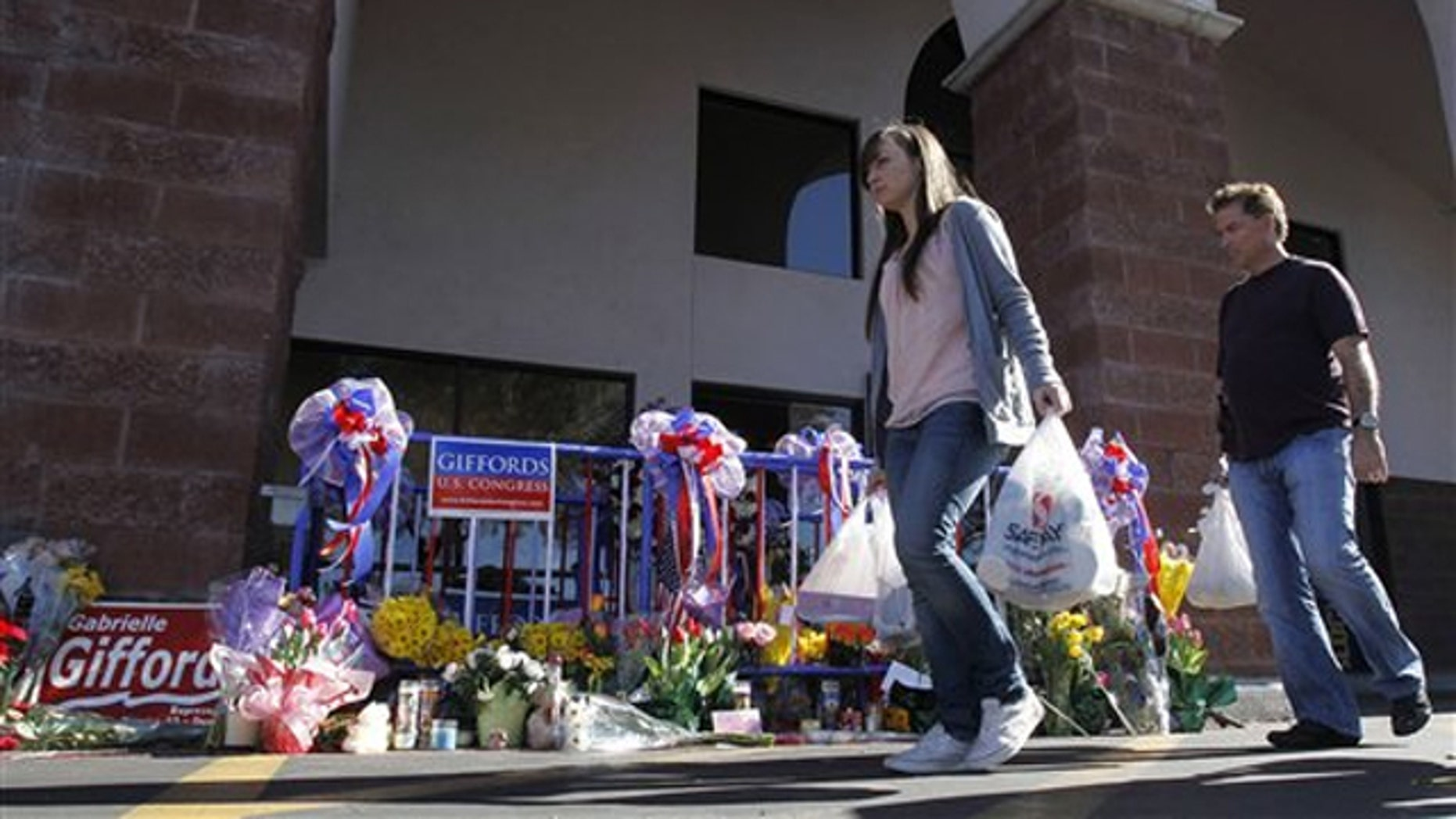 In this Jan. 15 photo, patrons walk past a makeshift memorial at the Safeway grocery store in Tucson where a gunman opened fire Jan. 8.