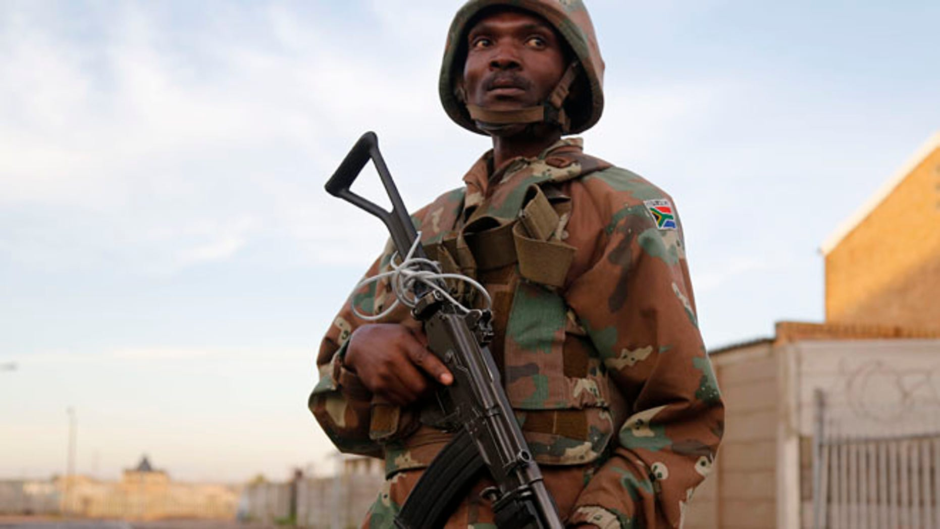 May 21, 2015: A South African soldier provide security for policemen as they look for drugs  in Manenberg, South Africa. (AP)