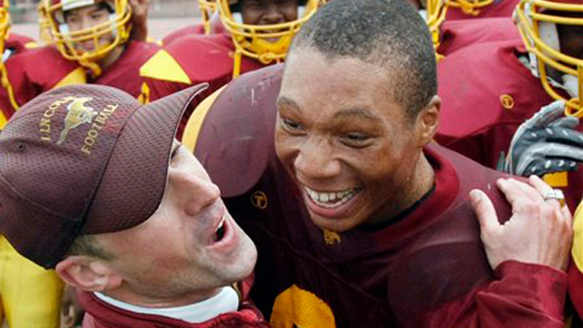 In this file photo taken Nov. 27, 2008, Lincoln Assistant Coach Kevin Doherty, left, hugs running back DeShon Marman as Lincoln defeated Washington in the annual Academic Athletic Association (AAA), San Francisco championship high school football game in San Francisco.