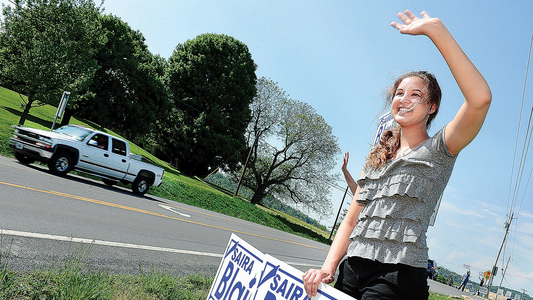 May 13, 2014:  Saira Blair, a 17-year-old student at Hedgesville High School, waves to motorists along Route 9 in Hedgesville, W. Va.
