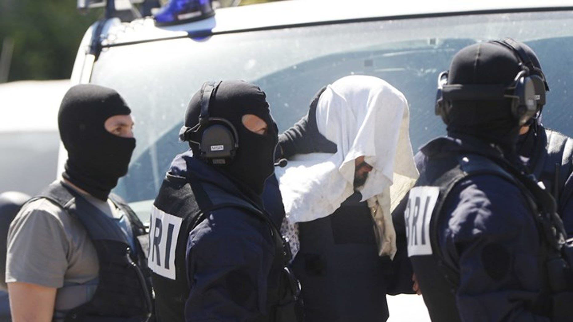 Yassin Salhi after his arrest in June, with a towel covering his head.
