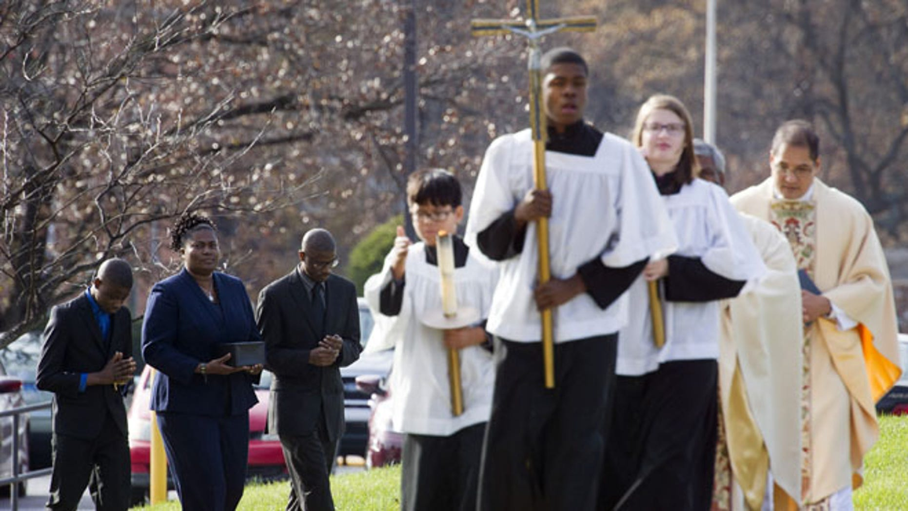 Nov. 29, 2014: Isatu Salia, second from left, carries the cremated remains of her husband, Dr. Martin Salia, while their sons Maada Martin Salia, 20, third from left, and Hinwaii Sakatty Salia, 12, left, walk with her to enter St. Mary's Catholic Church in Landover Hills, Md., during the funeral mass for Dr. Martin Salia. (AP)