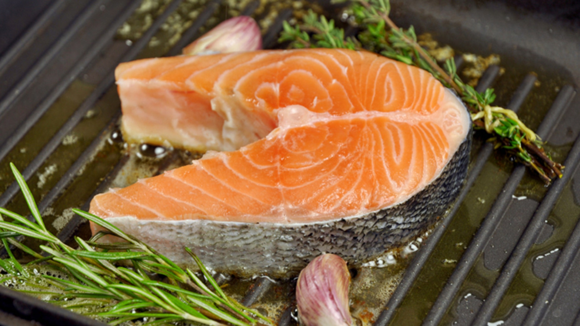 Salmon steak being fried in a pan with rosemary,thyme and garlic