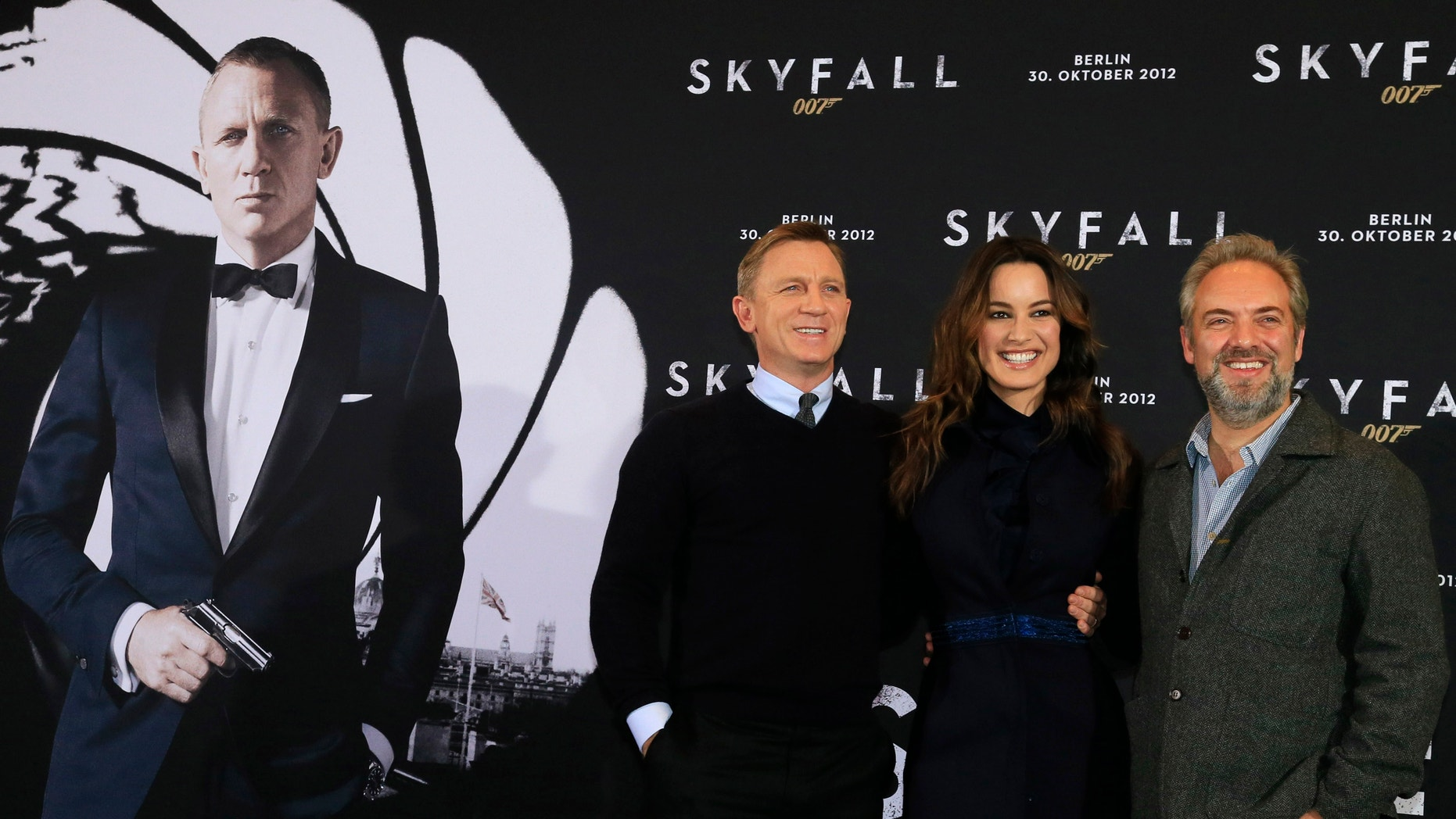 """Director Sam Mendes, right, poses with cast members Daniel Craig and Berenice Marlohe, center, during a photocall to promote their film """"Skyfall"""" in Berlin October 30, 2012."""