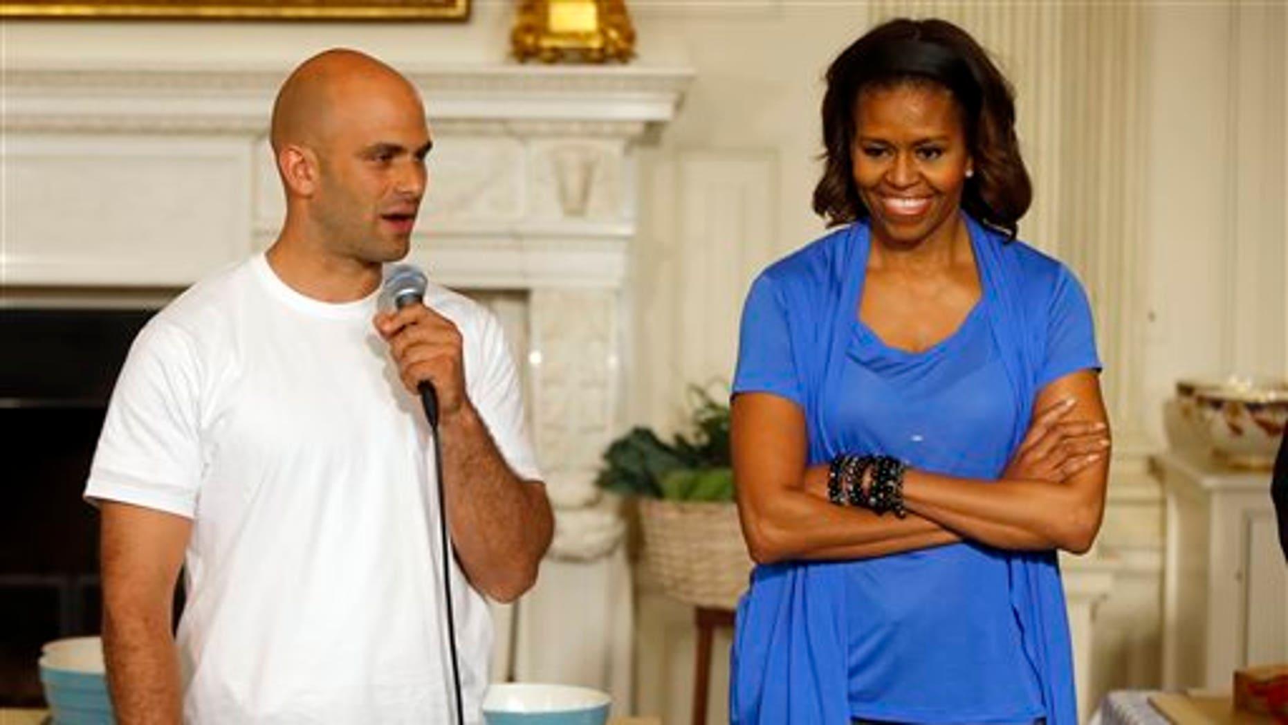 First lady Michelle Obama stands with Sam Kass, White House Senior Policy Adviser for Nutrition Policy, before they make salads from vegetables harvested from the White House garden with area students in the State Dining Room of the White House in Washington.