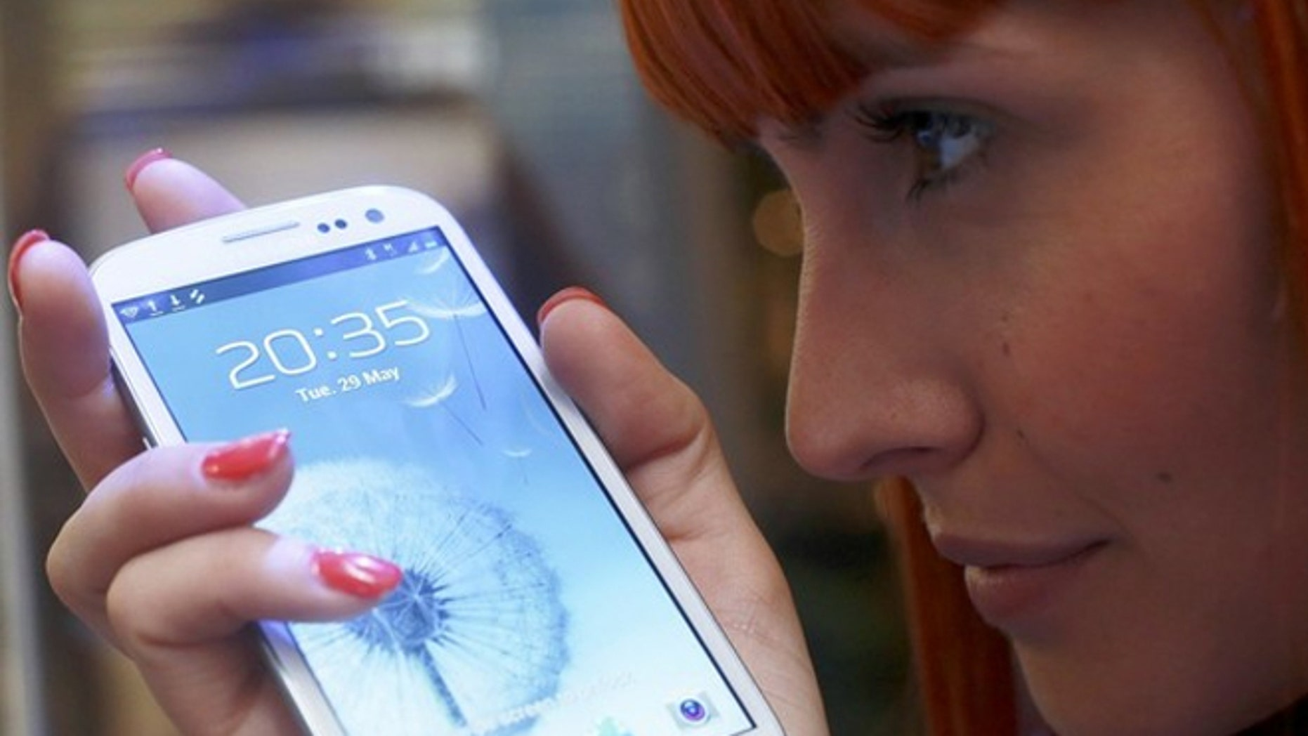 A shop assistant poses with the new Galaxy S III smartphone. Now Samsung wants to get in the social network game.