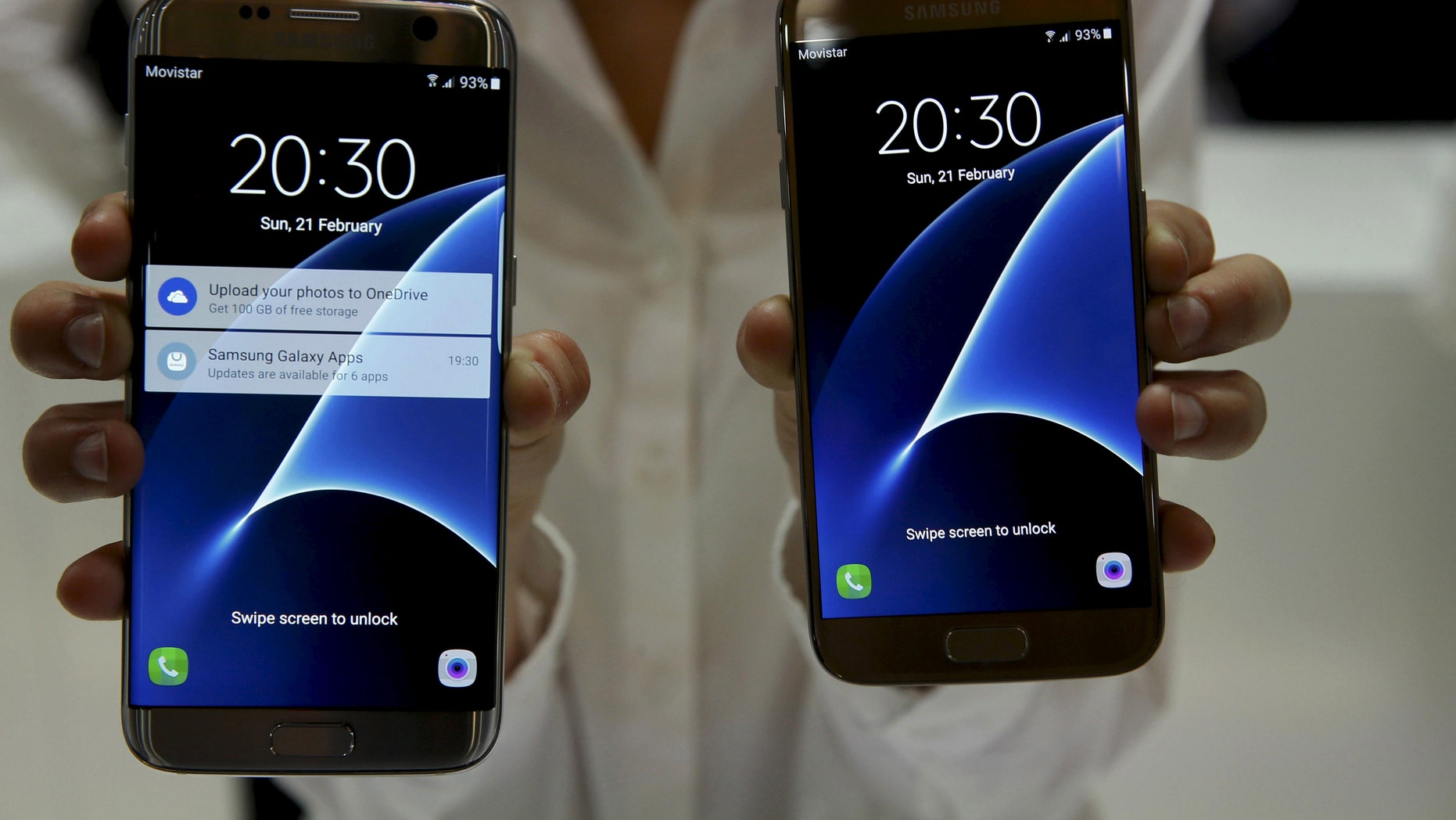 A woman displays new Samsung S7 (R) and S7 edge smartphones after their unveiling ceremony at the Mobile World Congress in Barcelona, Spain, Feb. 21, 2016. (REUTERS/Albert Gea)
