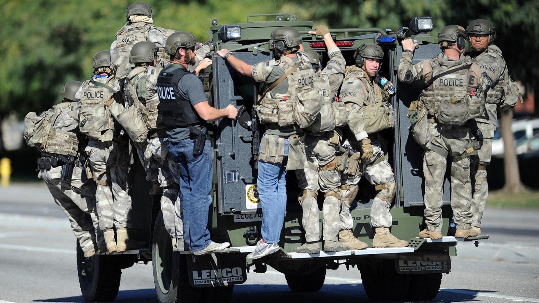 Dec. 2, 2015: An armored vehicle carries police officers near the scene of multiple shootings in San Bernardino, Calif.