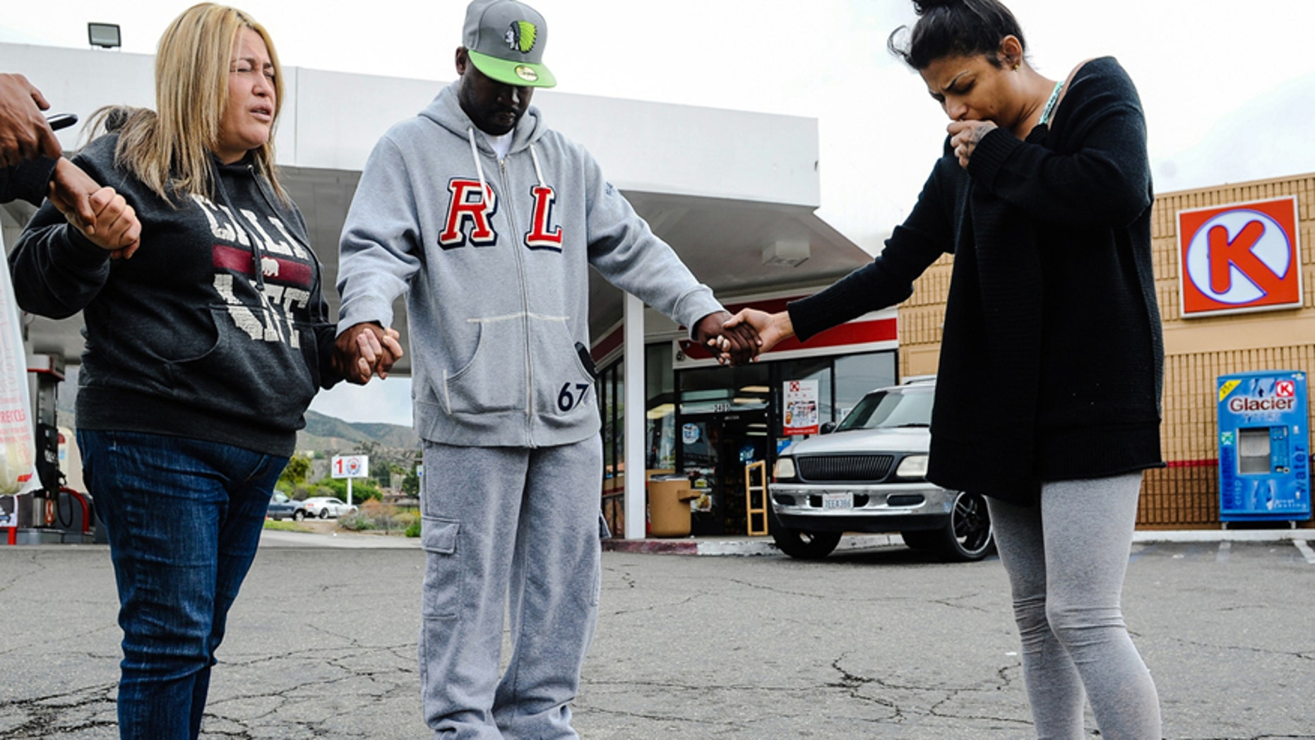 March 14, 2016: Francine Prieto-Estrada, left, leads Donald Pride and Elisa Castro in a prayer at memorial site for 12-year-old shooting victim Jason Spears at a Circle K in San Bernardino, Calif.