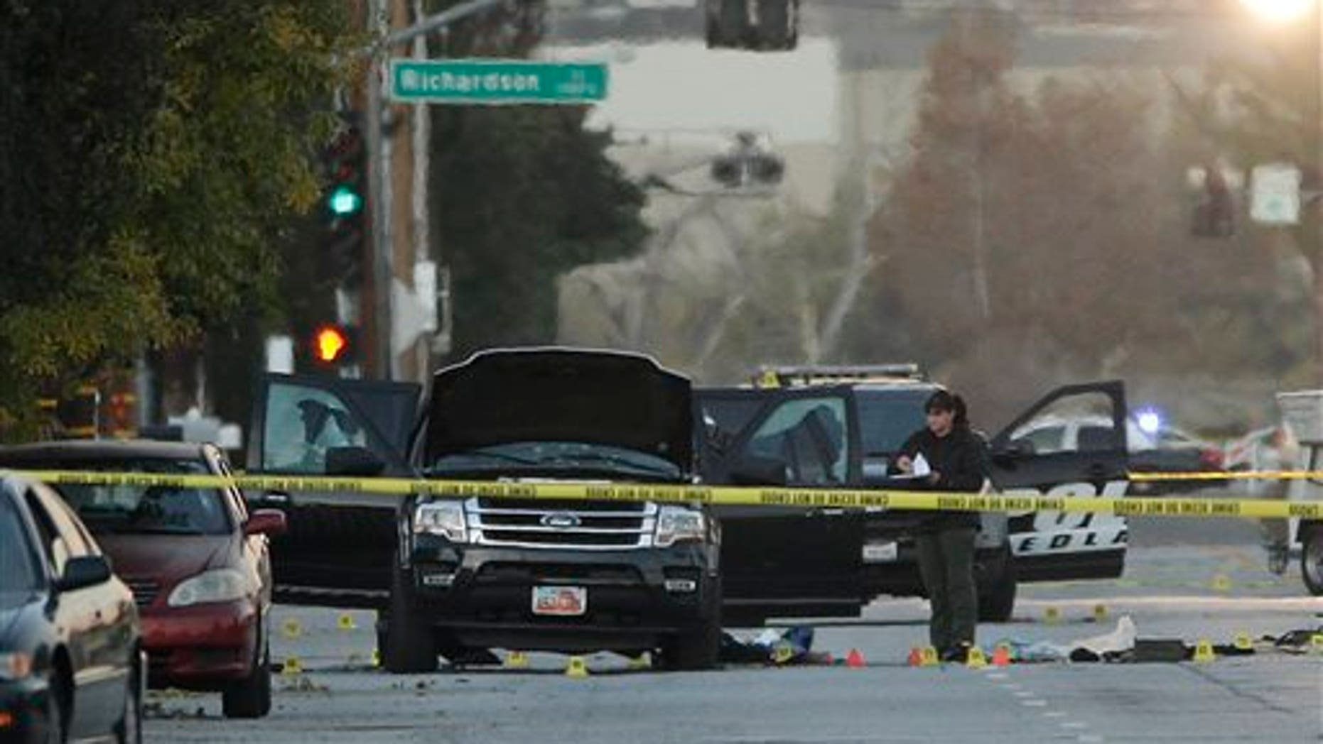 An investigator looks at a Black SUV that was involved in a police shootout with suspects, Thursday, Dec. 3, 2015, in San Bernardino, Calif.  A heavily armed man and woman opened fire Wednesday on a holiday banquet, killing multiple people and seriously wounding others in a precision assault, authorities said. Hours later, they died in a shootout with police.  (AP Photo/Jae C. Hong)