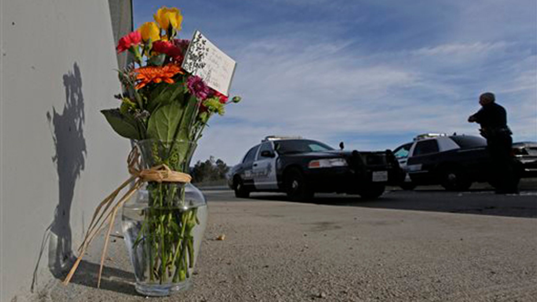 Dec. 3, 2015: Flowers are left by the side of the road as a San Bernardino police officer blocks the road leading to the site of yesterday's mass shooting in San Bernardino, Calif.