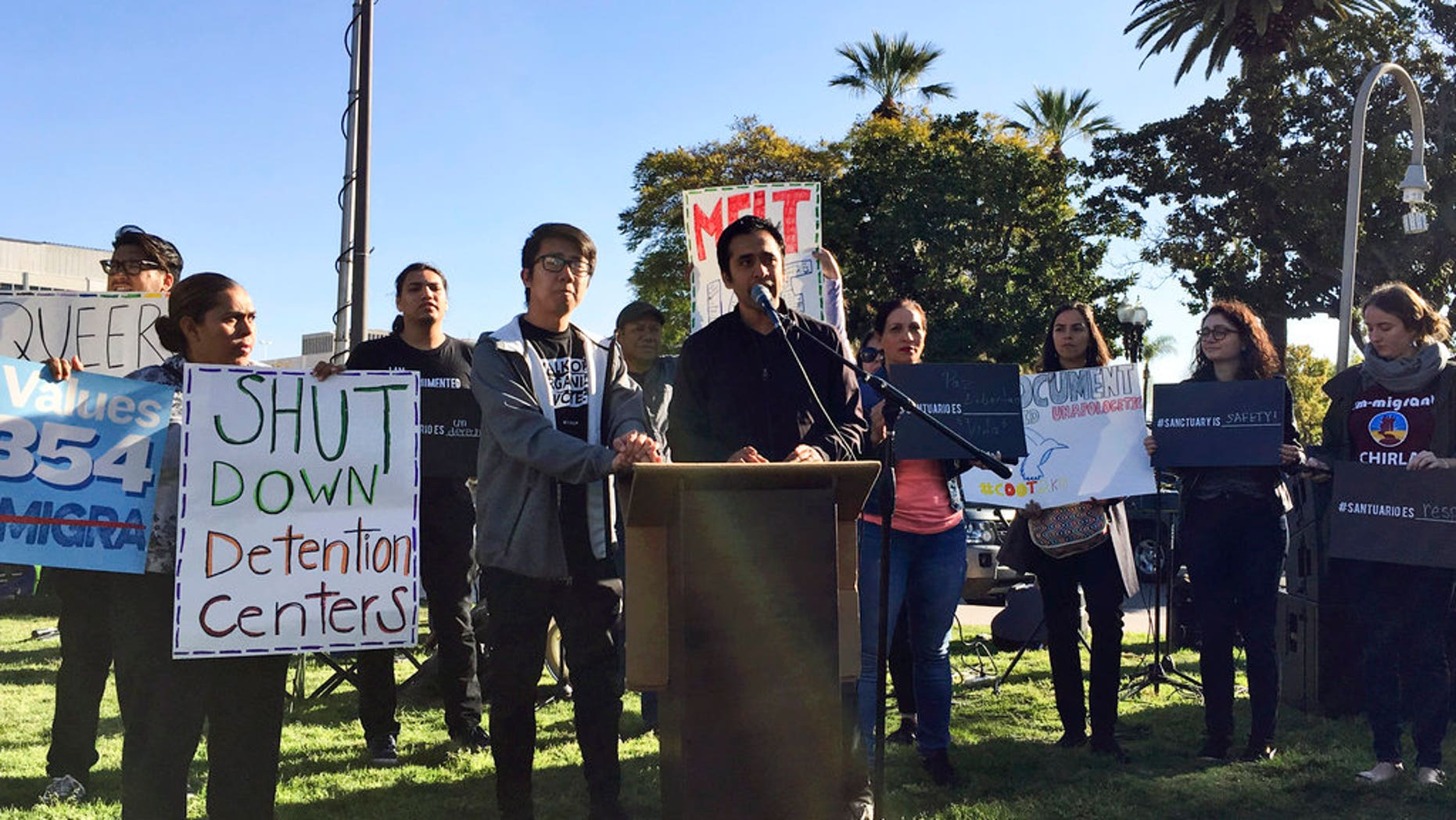 Salvador G. Sarmiento, center, speaks during an Immigrant advocates rally outside the Orange County Board of Supervisors' meeting room in Santa Ana, Calif., Tuesday, March 27, 2018, to protest a proposal to join a U.S. government lawsuit against California over the state's so-called sanctuary law. (AP Photo/Amy Taxin)