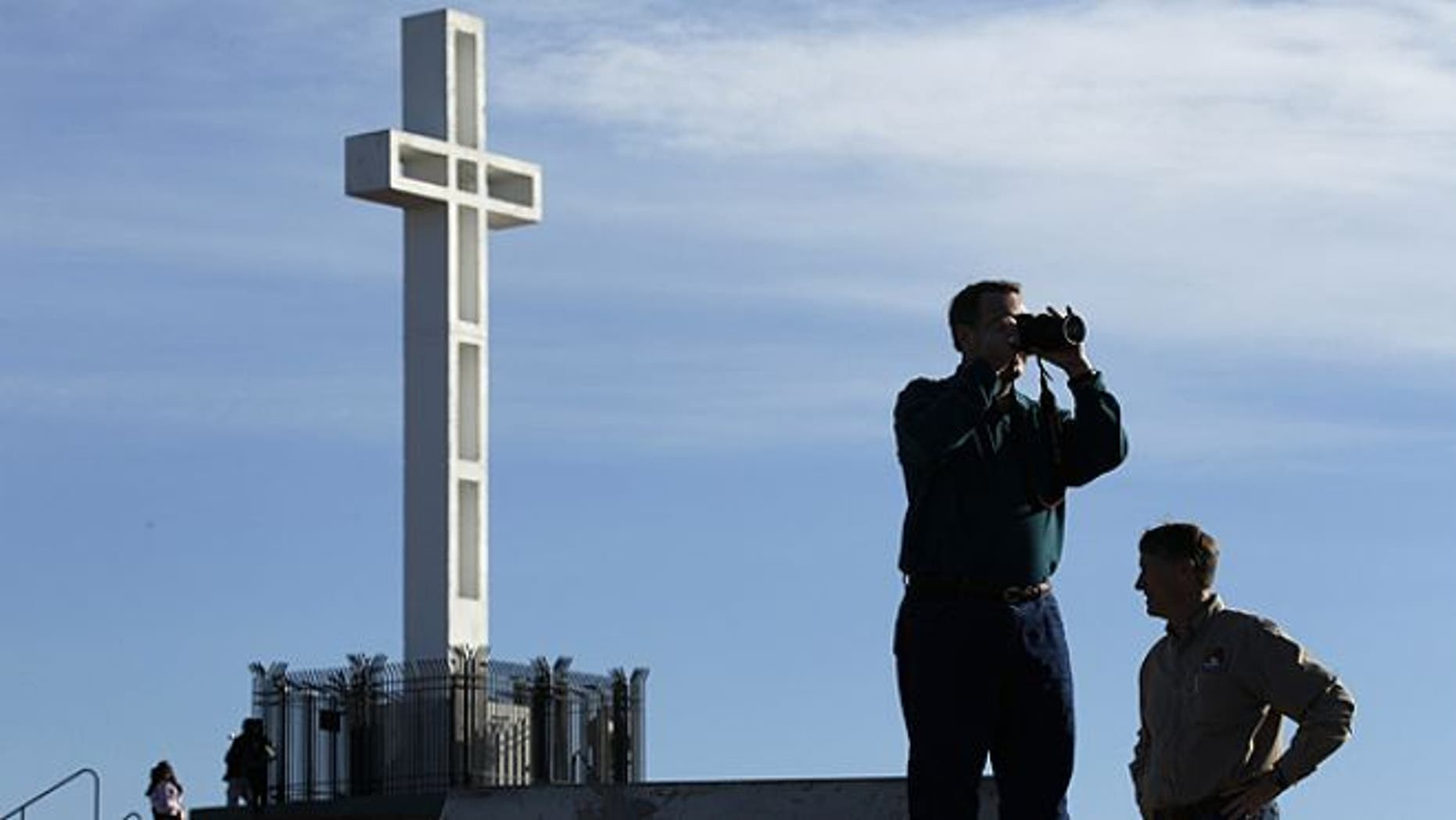 FILE: Jan. 4, 2011: Rev. John Fredericksen of Orlando, Fla., takes a picture in front of the war memorial cross on Mount Soledad in San Diego, alongside Burdette Streeter of San Diego.