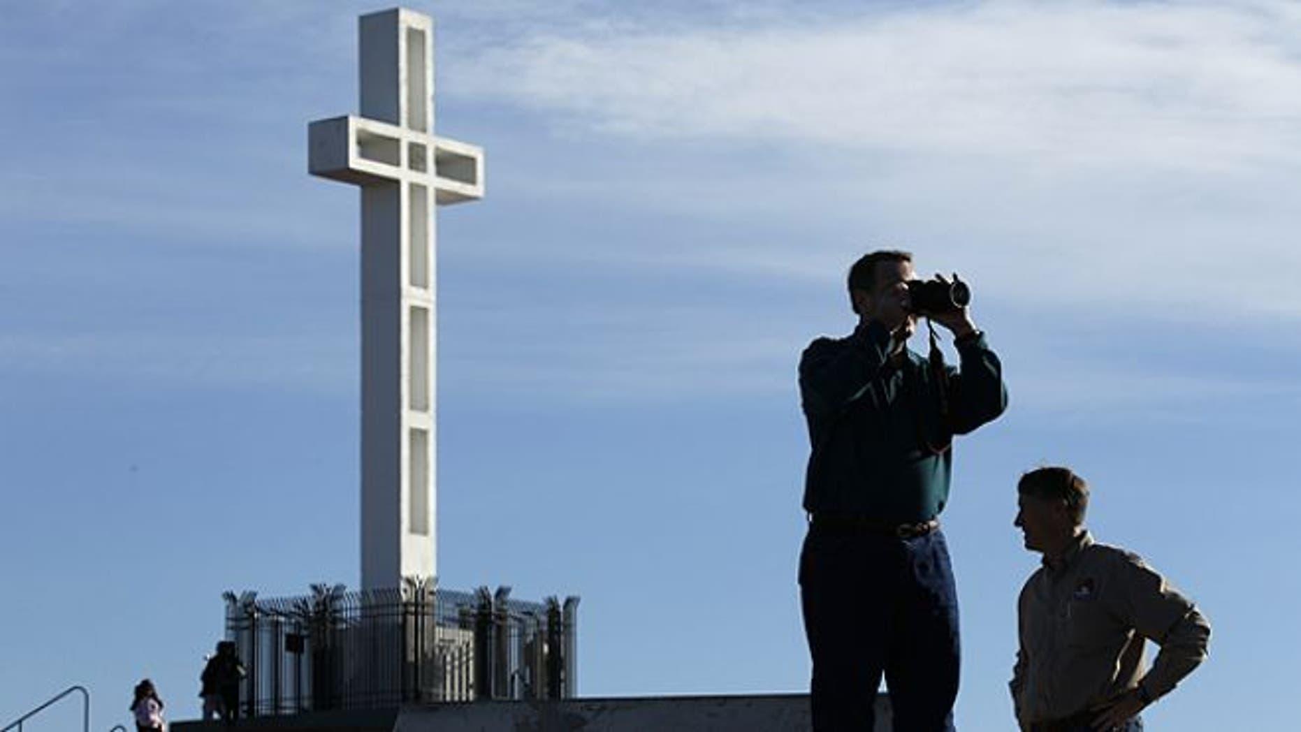 FILE: Jan. 4, 2011: Rev. John Fredericksen of Orlando, Fla., takes a picture in front of the war memorial cross on Mount Soledad in San Diego, alongside Burdette Streeter of San Diego.