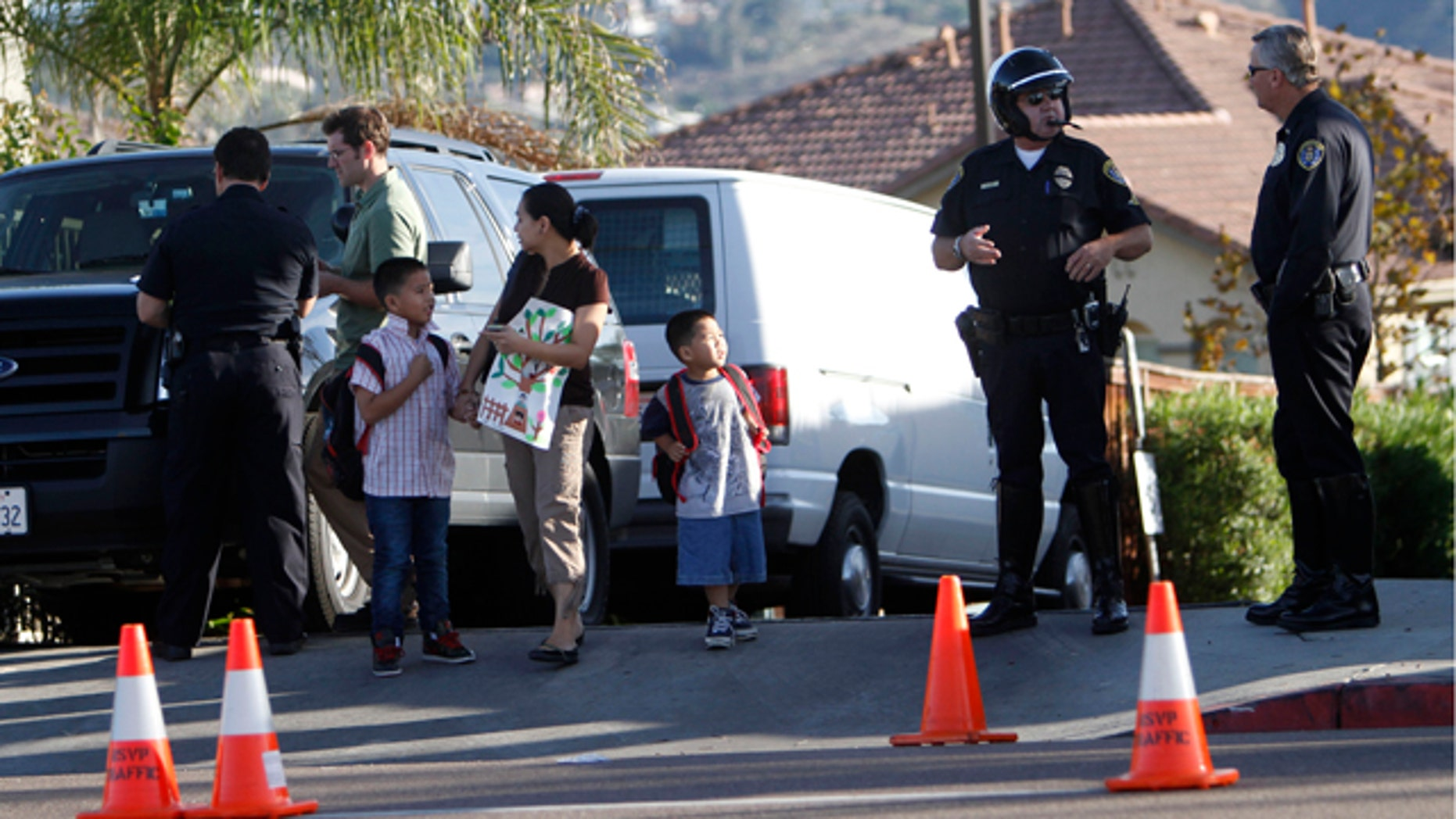 Oct. 28: A woman walks her children out of an apartment complex and past San Diego police officers where a shootout resulted in the death of a police officer, his suspected killer and another person.