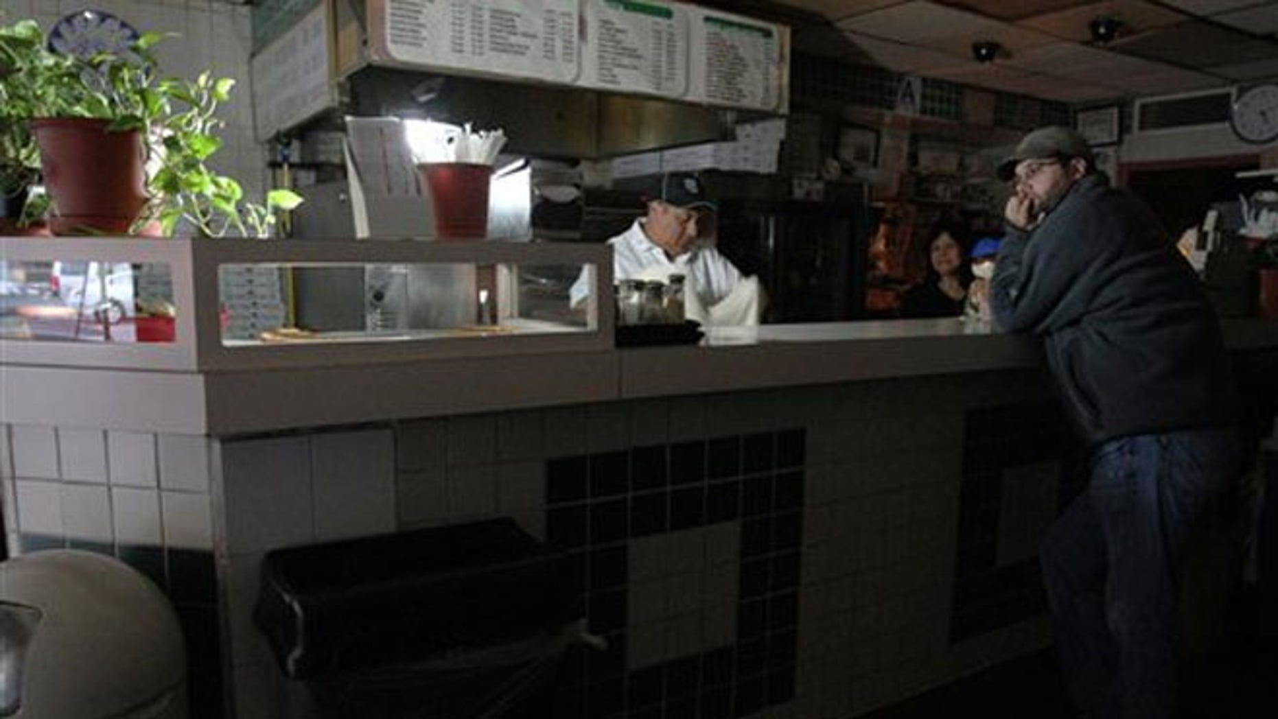 Oct. 31, 2012: Leigh Dworkin, right, waits for a slice of pizza as Carlos Quizhplema, left, and Rosa Rosas work behind the counter at Frank's Trattoria, in New York.