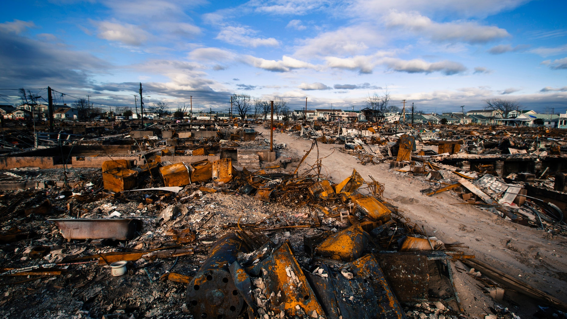 Clouds roll over destroyed homes after superstorm Sandy caused damage in the region of Breezy Point of Queens borough, New York.