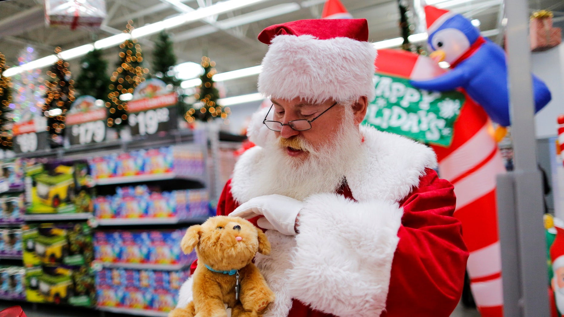 A man dressed as Santa Claus pets a toy as products are display for Christmas season at a Walmart store in Teterboro, New Jersey, U.S., October 26, 2016.