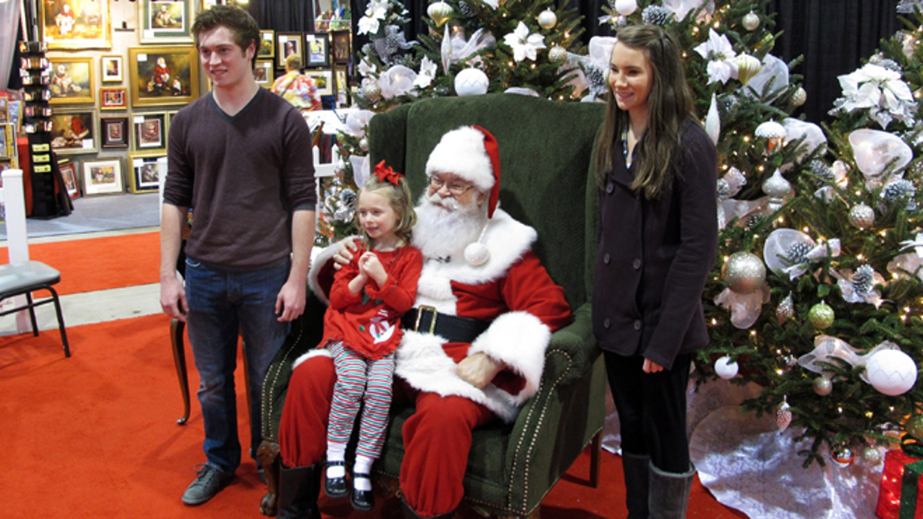 """In Nov. 29, 2013 photo taken from video, siblings Maddie, 5, Mackenzie, 15, and Caleb Bunn, 18, from Rocky Mount, N.C., pose for a photo with """"Santa"""" Cliff Snider at the Christmas Carousel show in Raleigh, N.C."""
