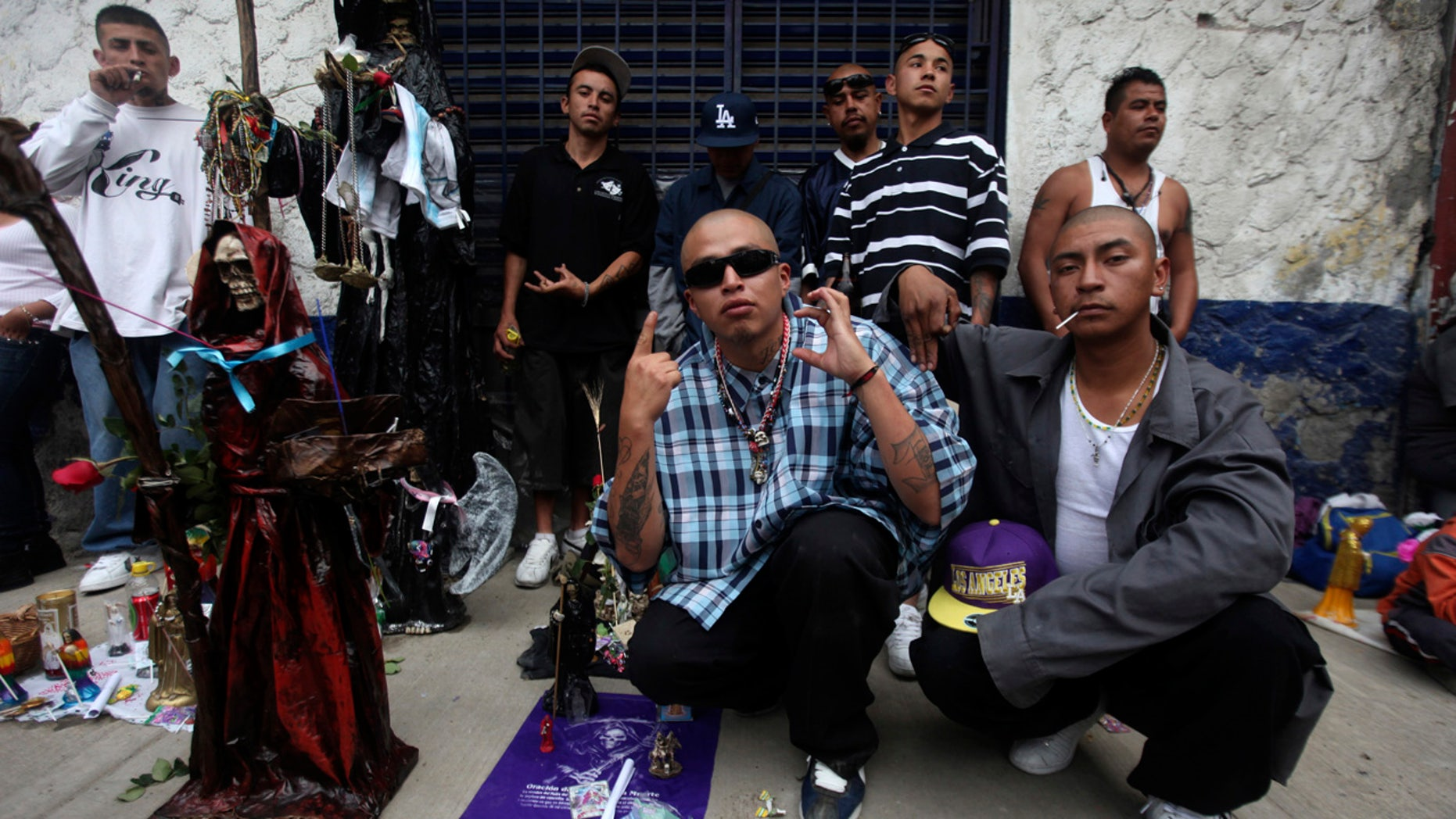 Followers of La Santa Muerte, a cult figure often depicted as a skeletal grim reaper, gesture while posing at the saint's altar in a Mexico City neighborhood.